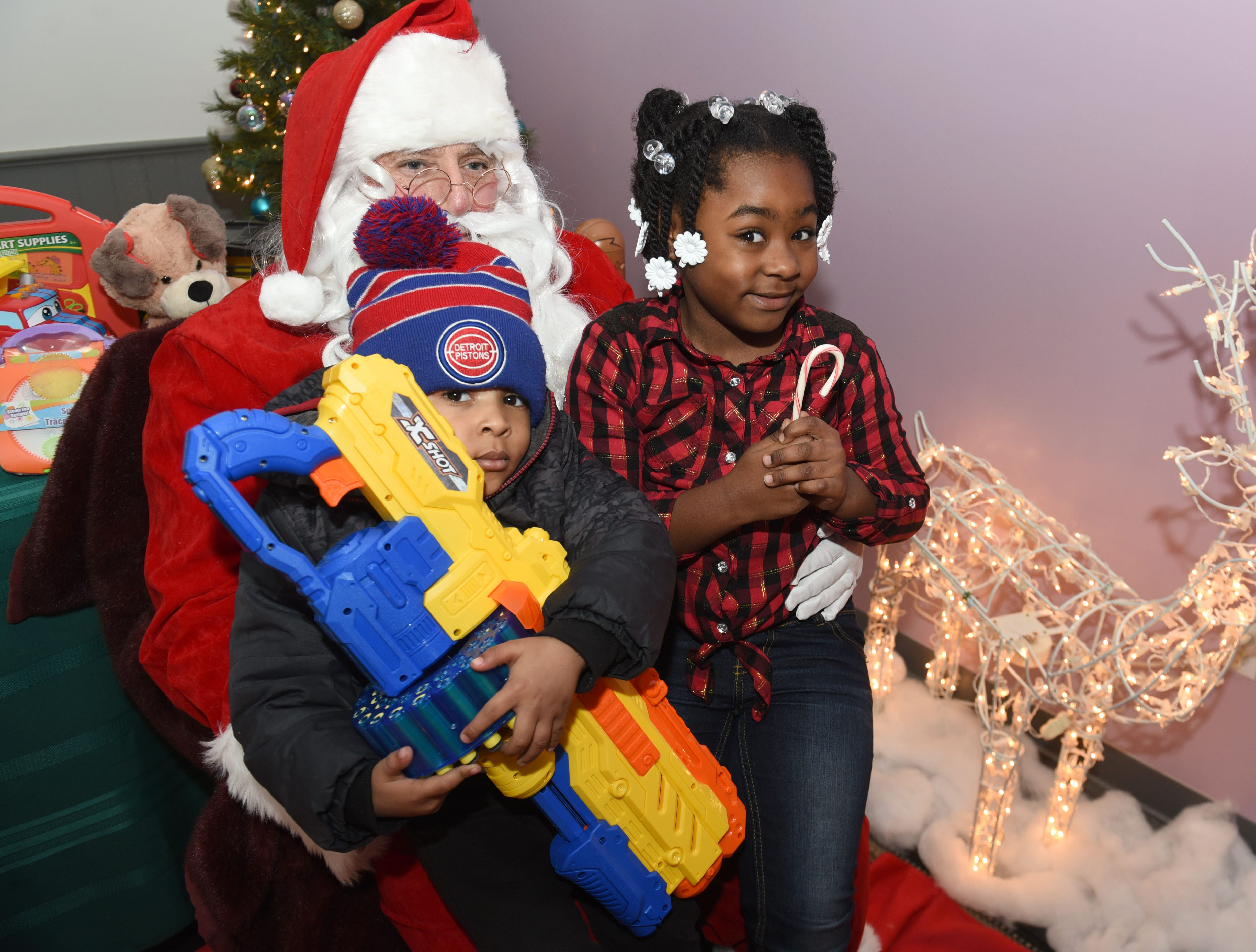 Shane Gilford (left), 3, and his sister Shayna get an early visit with Santa Claus at the Mosaic Midtown during Noel Night.