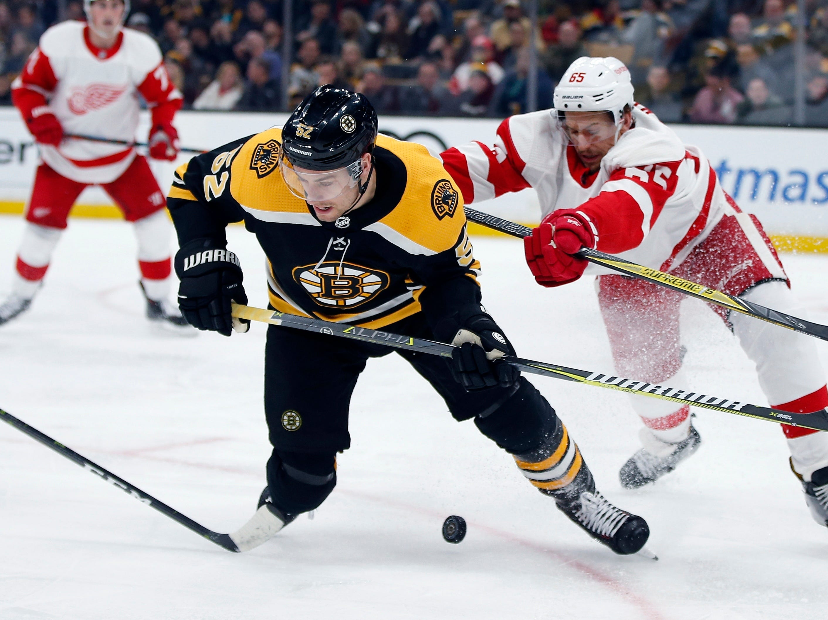 Detroit Red Wings' Danny DeKeyser (65) checks Boston Bruins' Sean Kuraly (52) during the second period.