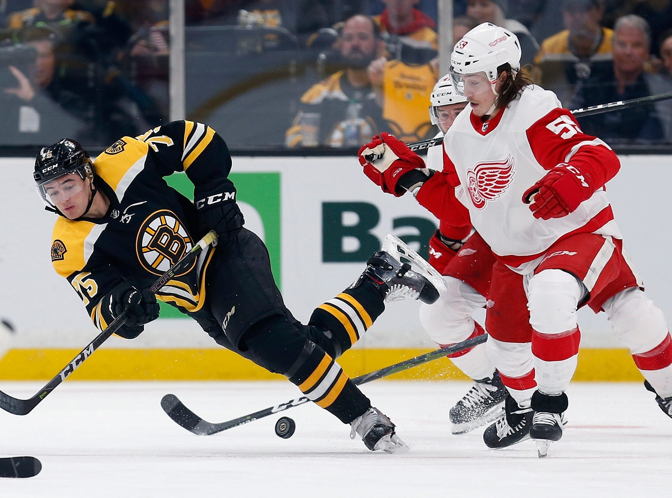 Boston Bruins' Connor Clifton (75) and Detroit Red Wings' Tyler Bertuzzi (59) battle for the puck during the second period.