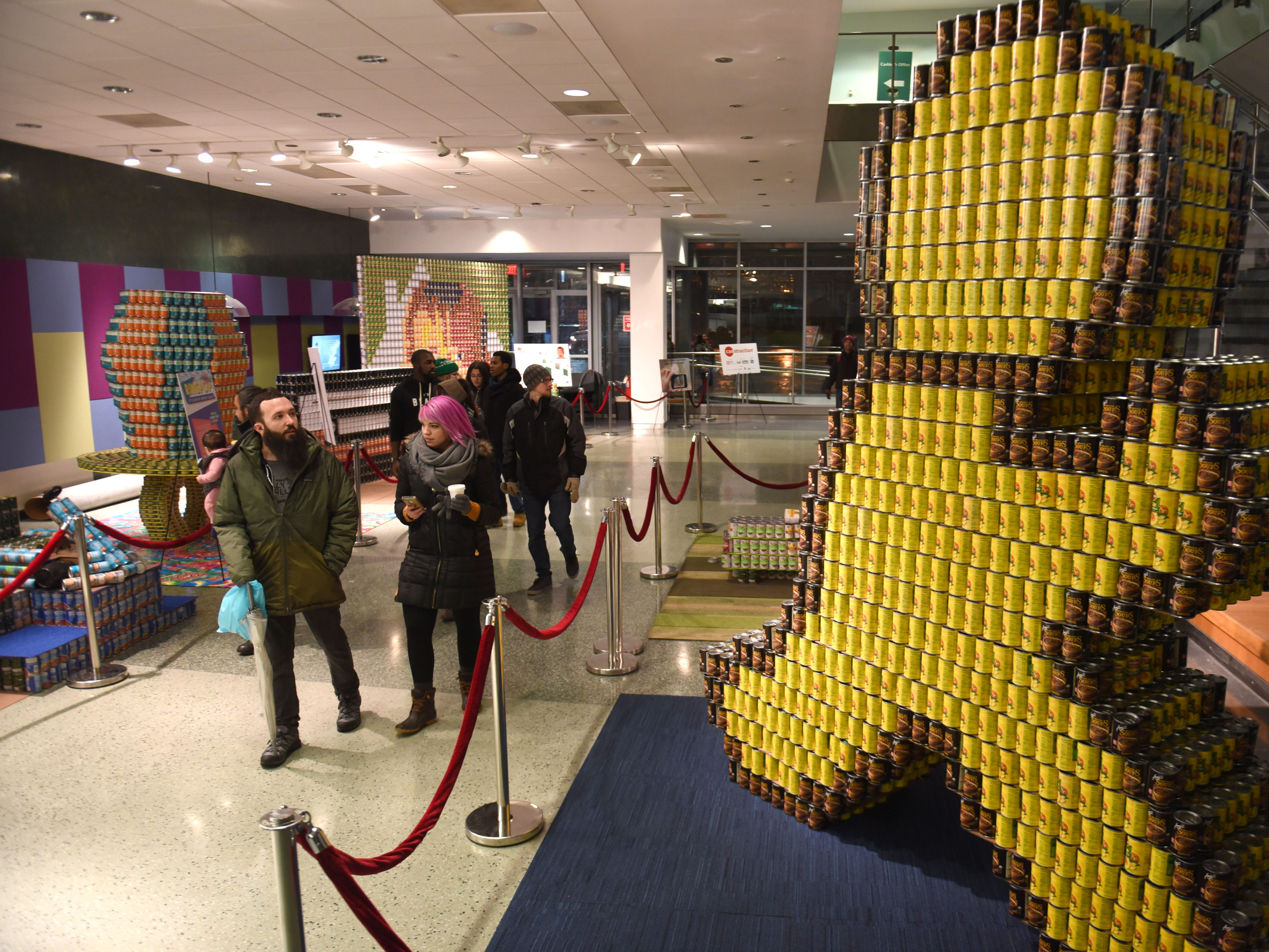 The can-struction display showcases a giant AOL messenger figure made of donated cans inside Wayne State University's Welcome Center  which benefits Gleaners Food Bank during Noel Night.
