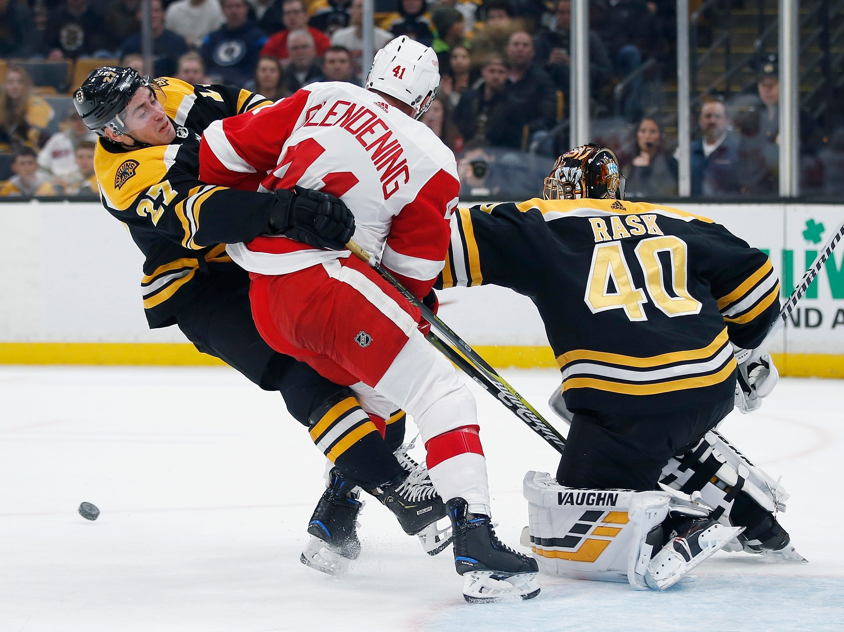 Boston Bruins' John Moore (27) blocks Detroit Red Wings' Luke Glendening from the rebound off goalie Tuukka Rask (40) during the first period.