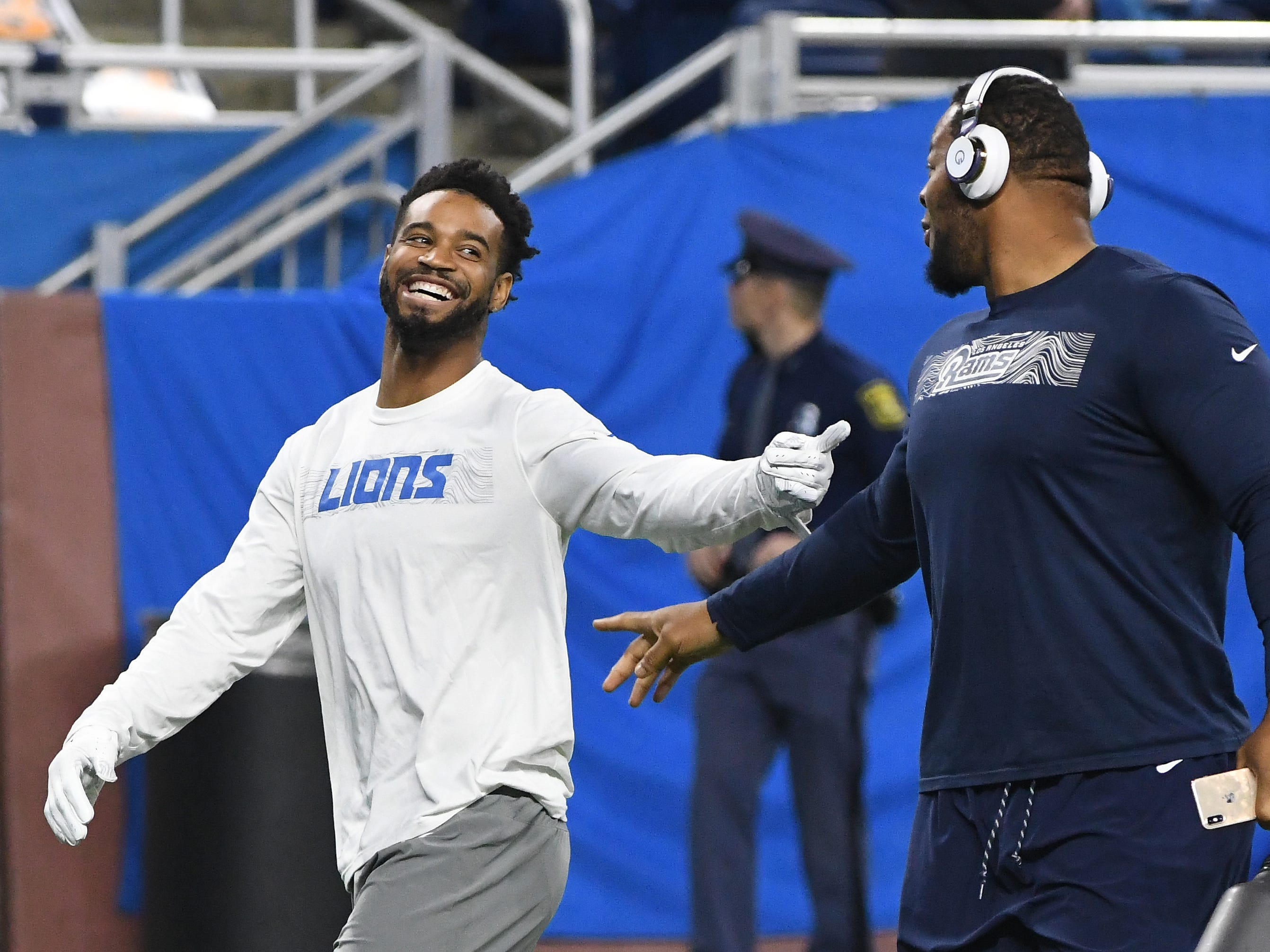 Lions' cornerback Darius Slay and former Detroit Lions, Los Angeles defensive tackle Ndamukong Suh chat as they leave the field after warmups.