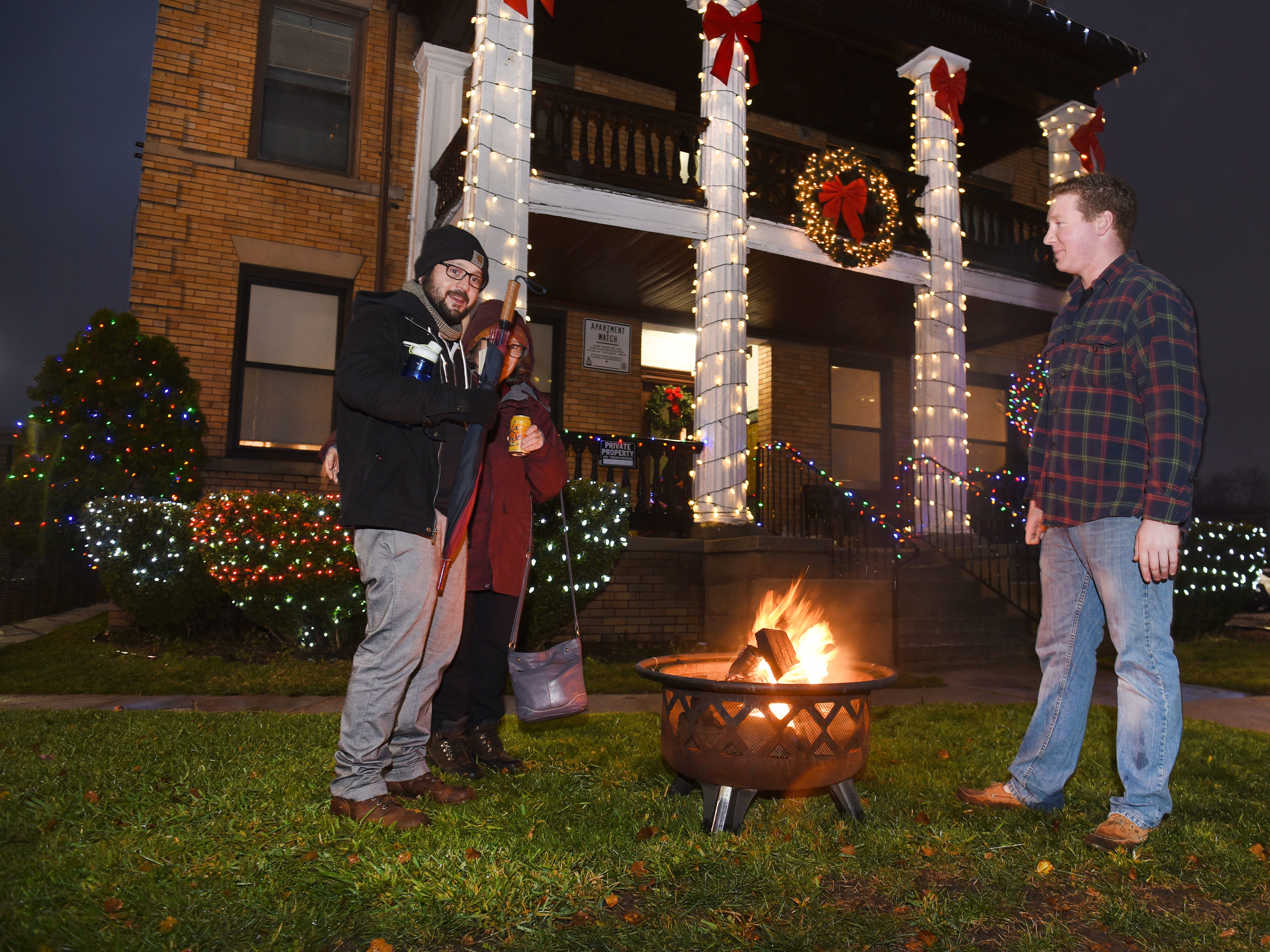 A bright fire burns outside the Christmas decorated Carrick Apartments along Cass Avenue as people brave the cold  during Noel Night in midtown Detroit.