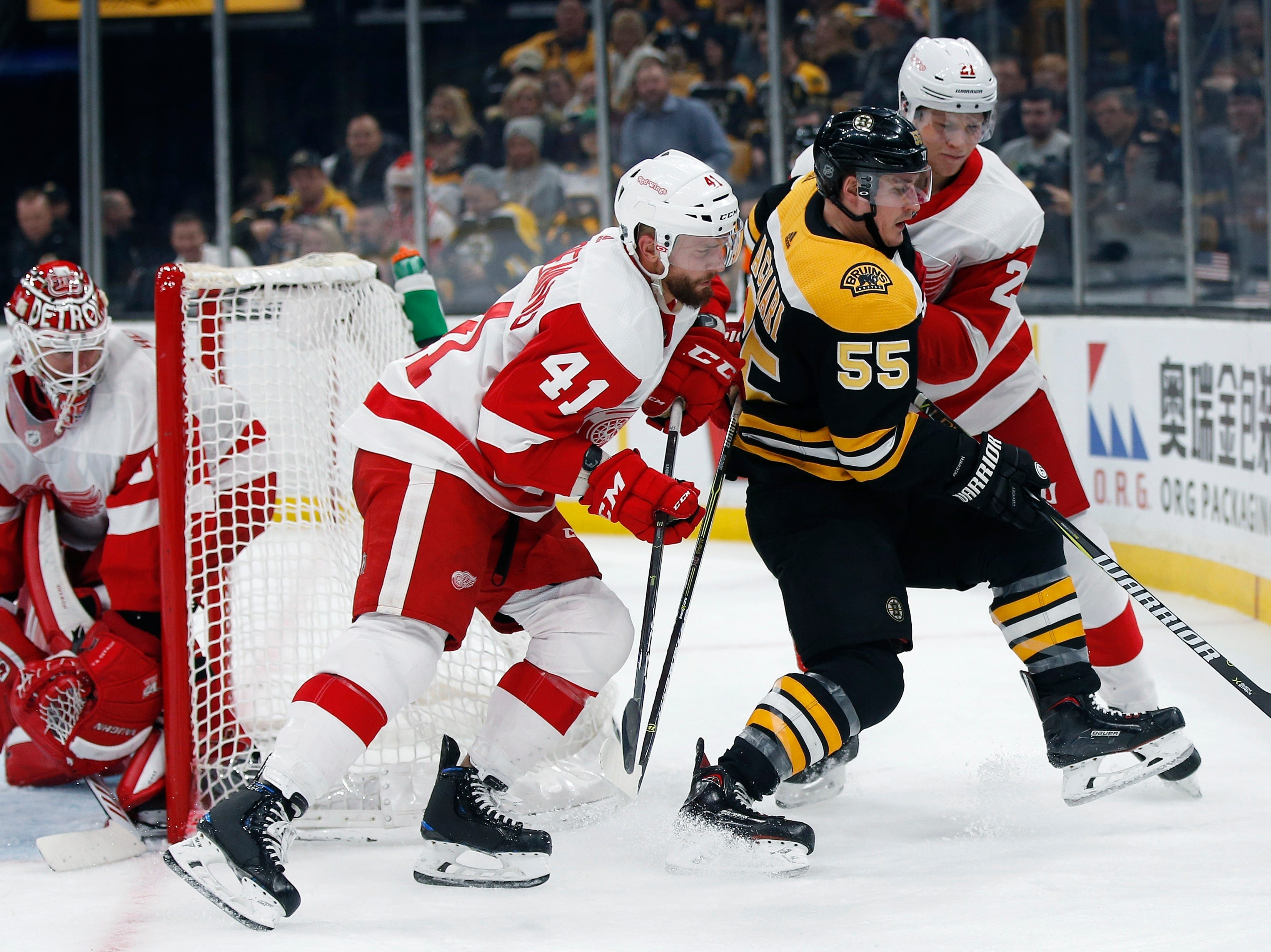 Boston Bruins' Noel Acciari (55) battles Detroit Red Wings' Luke Glendening (41) and Dennis Cholowski (21) for the puck during the second period.