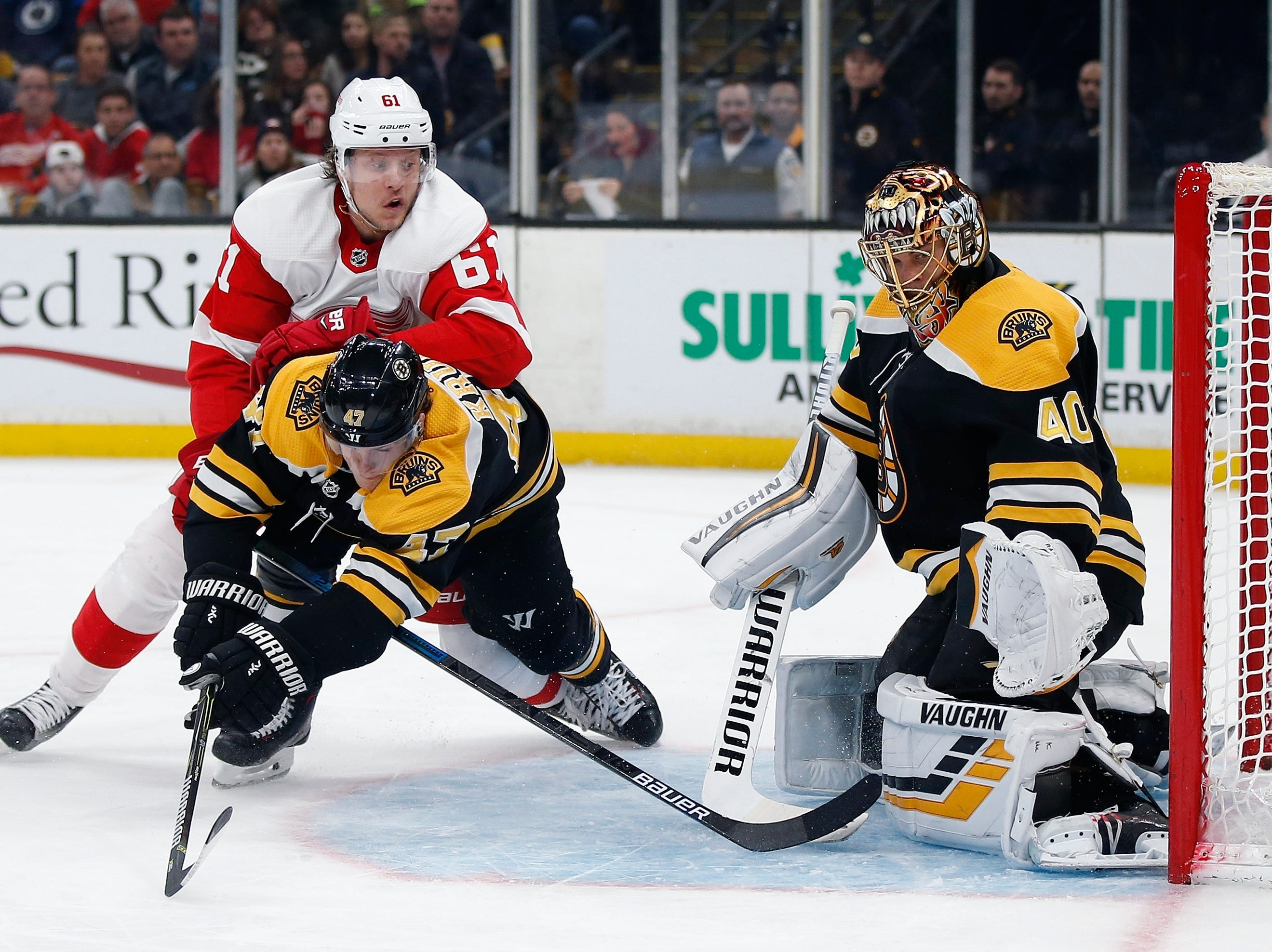 Detroit Red Wings' Jacob de la Rose (61) and Boston Bruins' Torey Krug (47) battle for the puck in front of Tuukka Rask (40) during the third period.