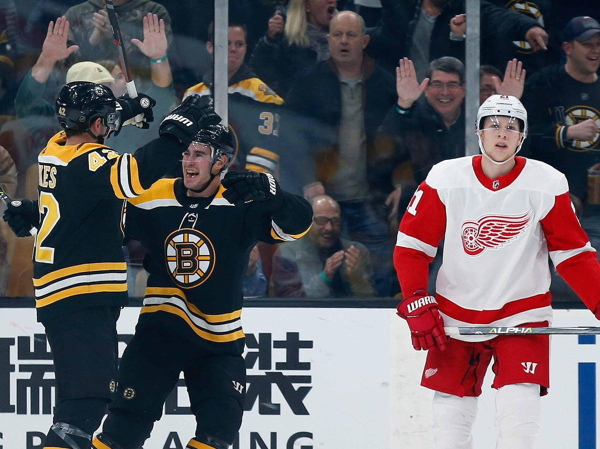 Boston Bruins' David Backes (42) celebrates his goal with teammate John Moore as Detroit Red Wings' Dennis Cholowski (21) skates away during the first period.