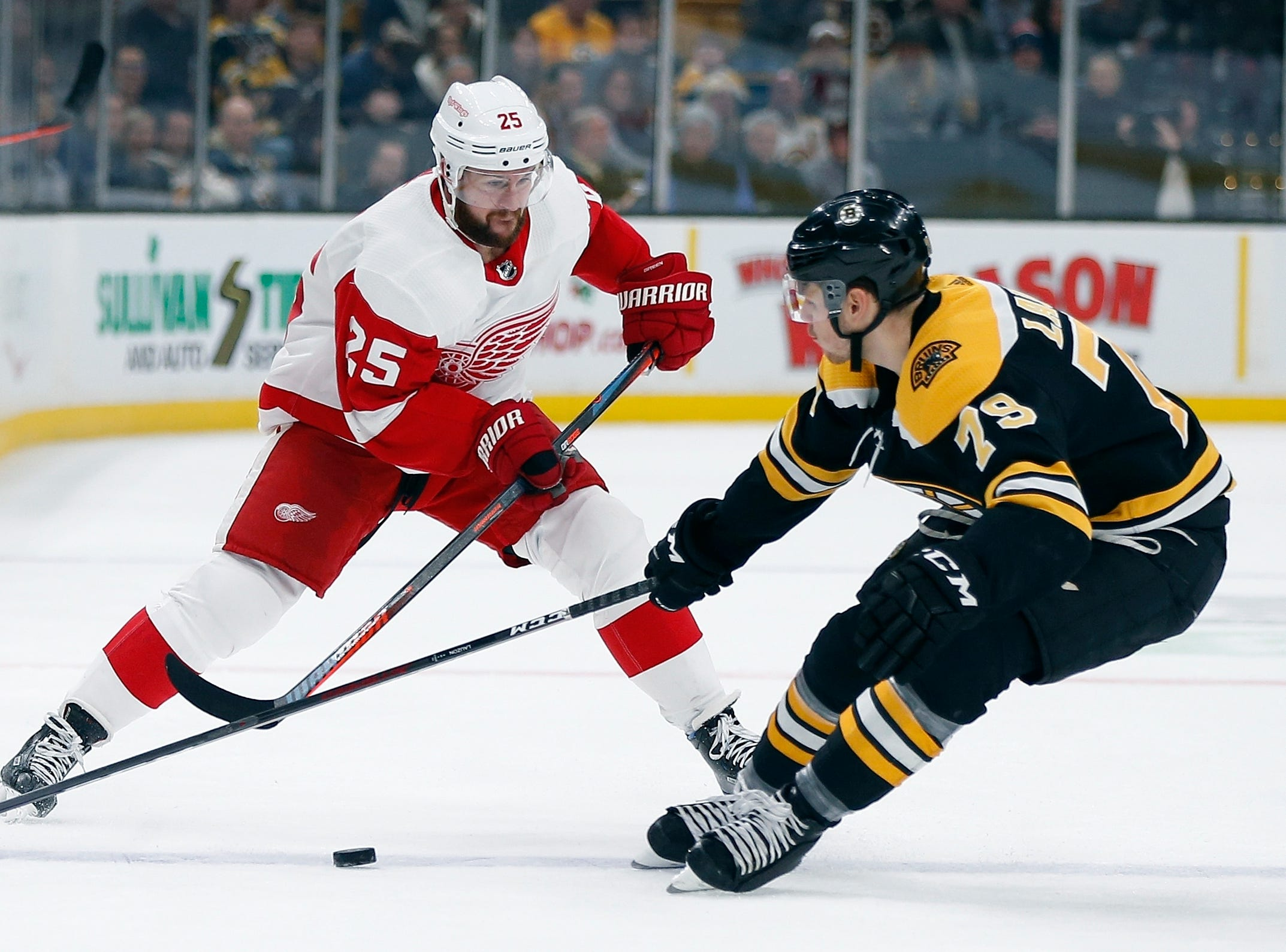 Detroit Red Wings' Mike Green (25) and Boston Bruins' Jeremy Lauzon (79) battle for the puck during the first period.