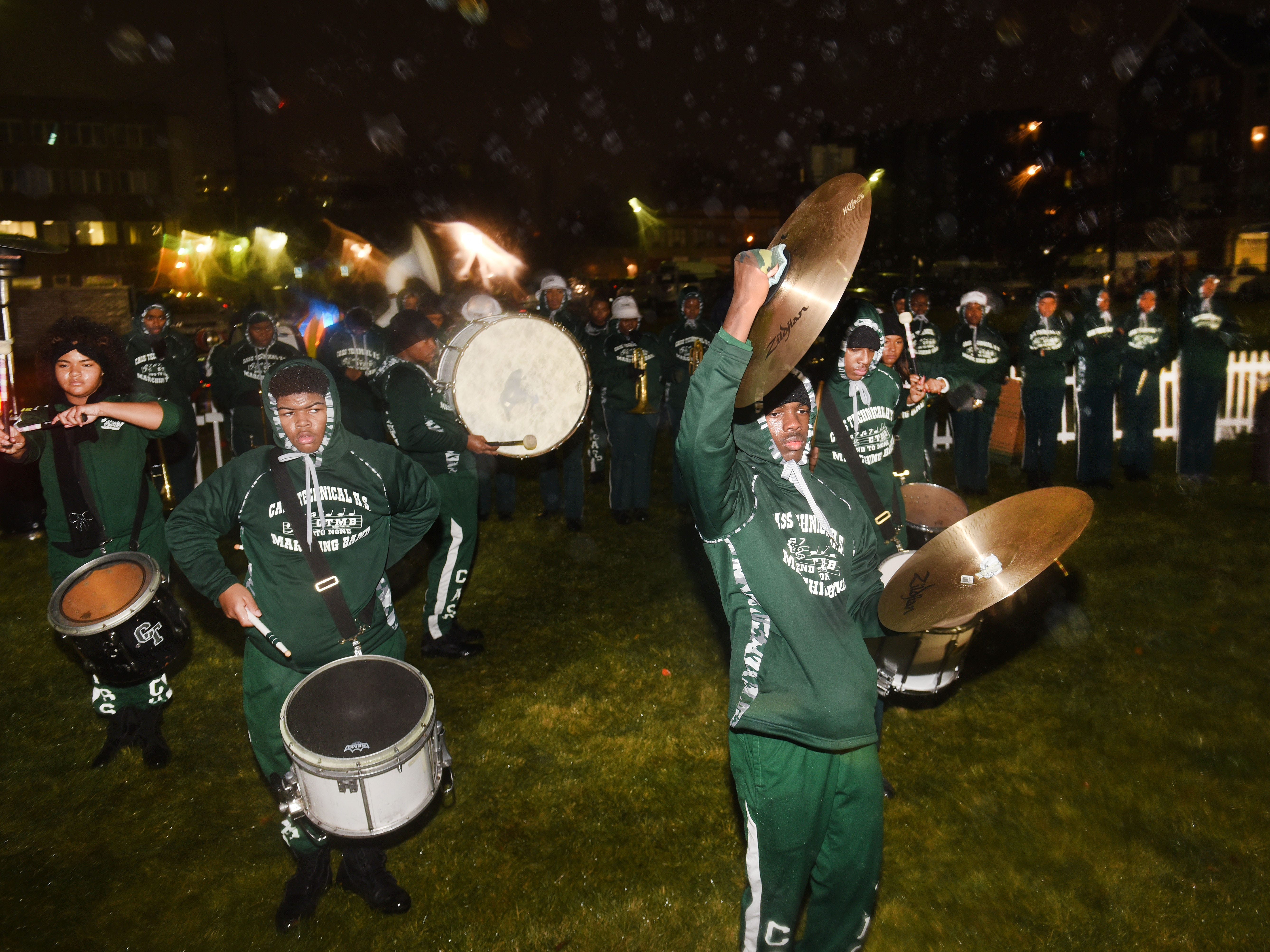 Members of the Cass Tech High School Marching Band perform in heavy rain during Noel Night along Woodward and Warren Avenue.