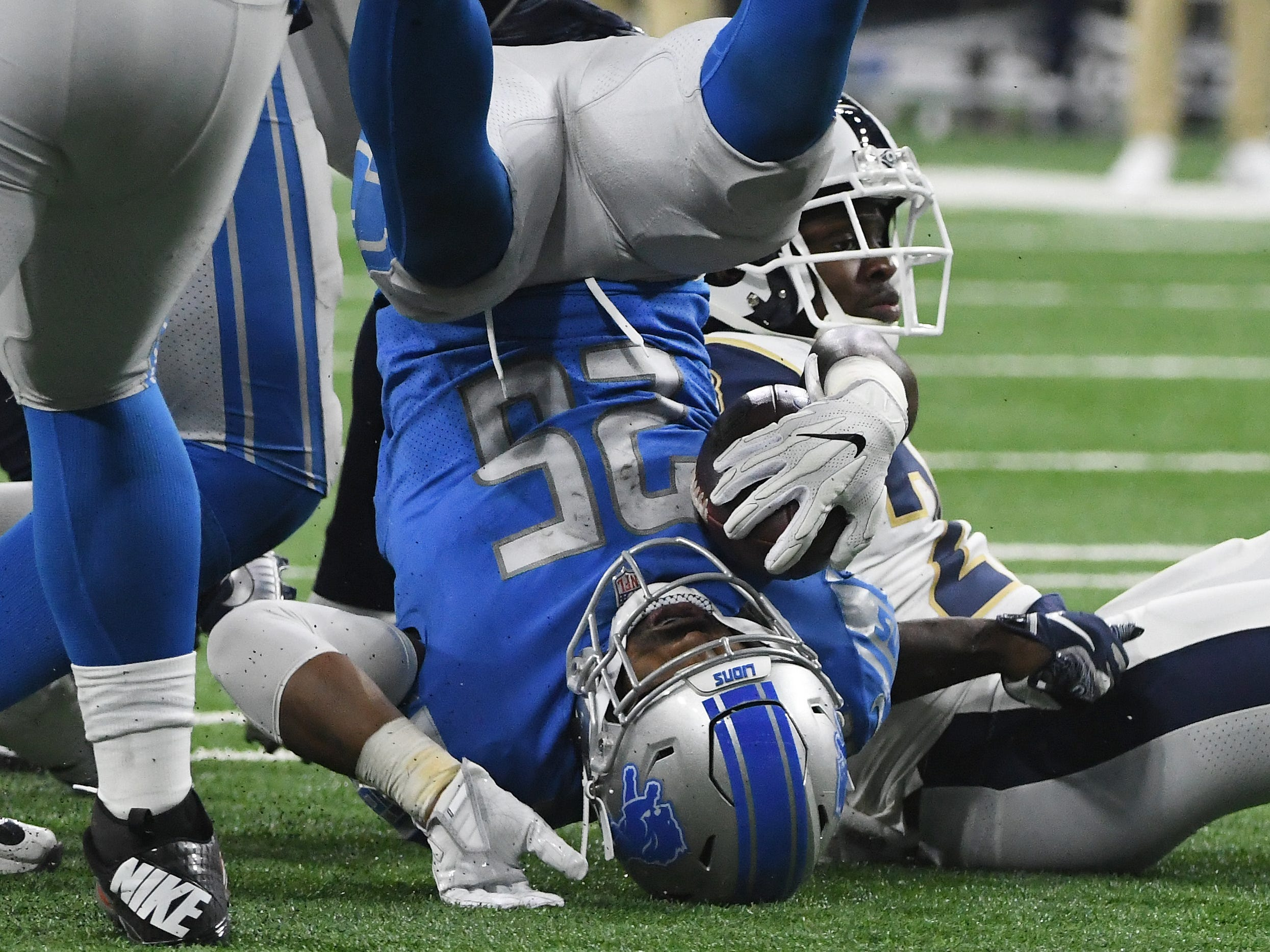 Lions running back Theo Riddick is upended after a run in the third quarter.