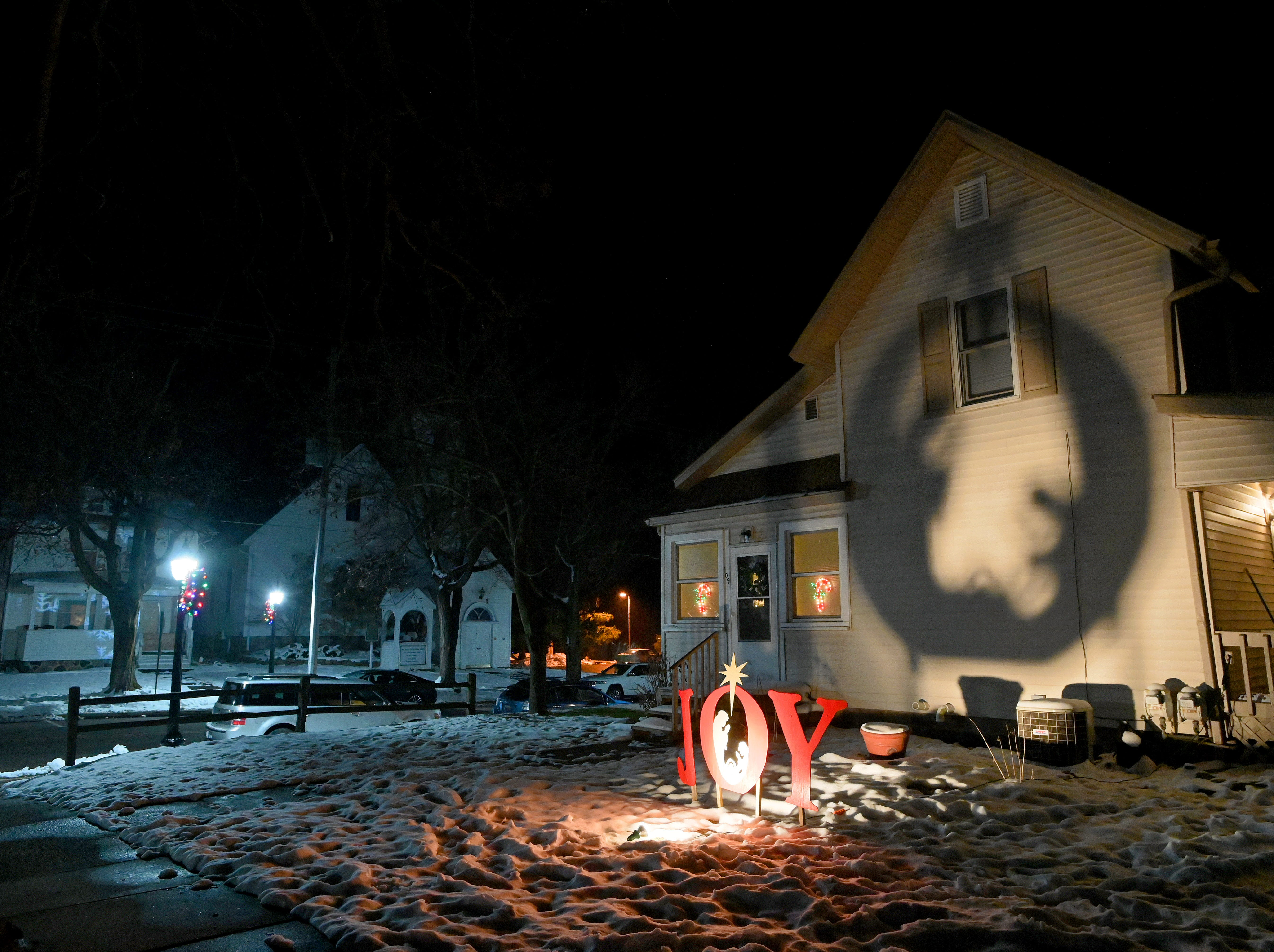 Not all holiday lighting is constructed of thousands of tiny LEDs — this handmade Christmas display, cut from plywood sheets, casts a giant shadow on a home in downtown Dimondale, Michigan.