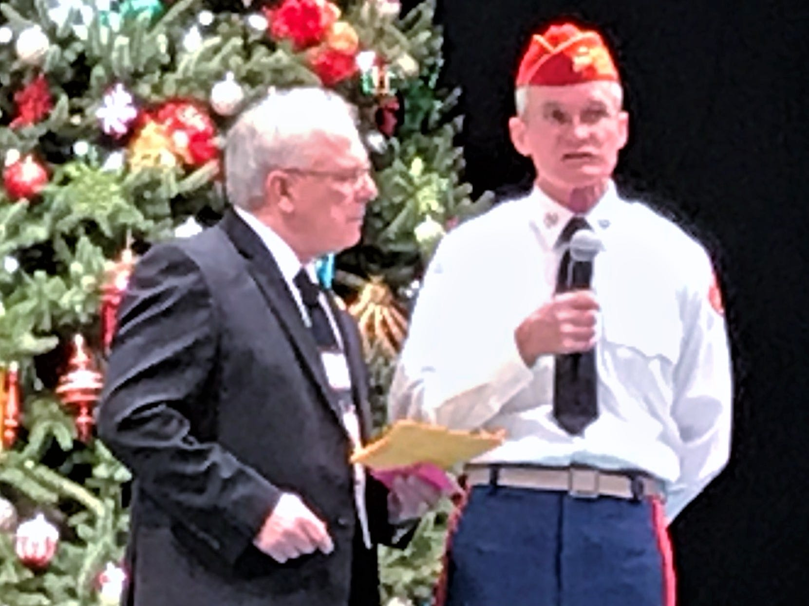 Matthew McInerny of the E.J. Brewer Detachment of the Marine Corps League presents a $500 check to Master of Ceremonies Tom Bruner during Sunday's Arctic League broadcast.