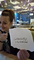Catfish Willy's manager Angela Melvin enjoys the affectionate notes diners often leave on the paper table covers at the seafood shack.