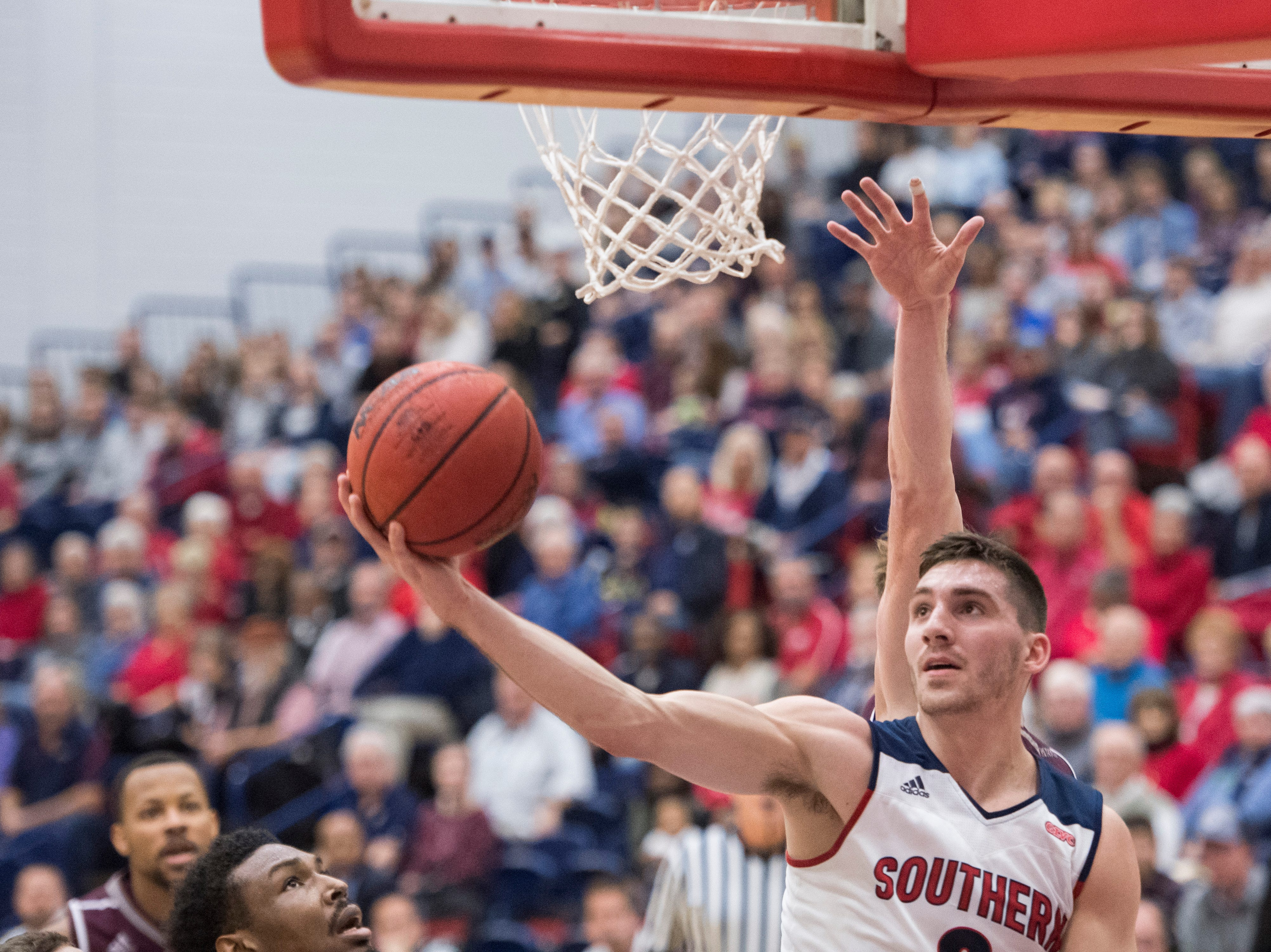 USI's Jacob Norman (2) hooks the ball from under the basket during the USI vs Bellarmine basketball game at the PAC Saturday, Dec. 1, 2018.