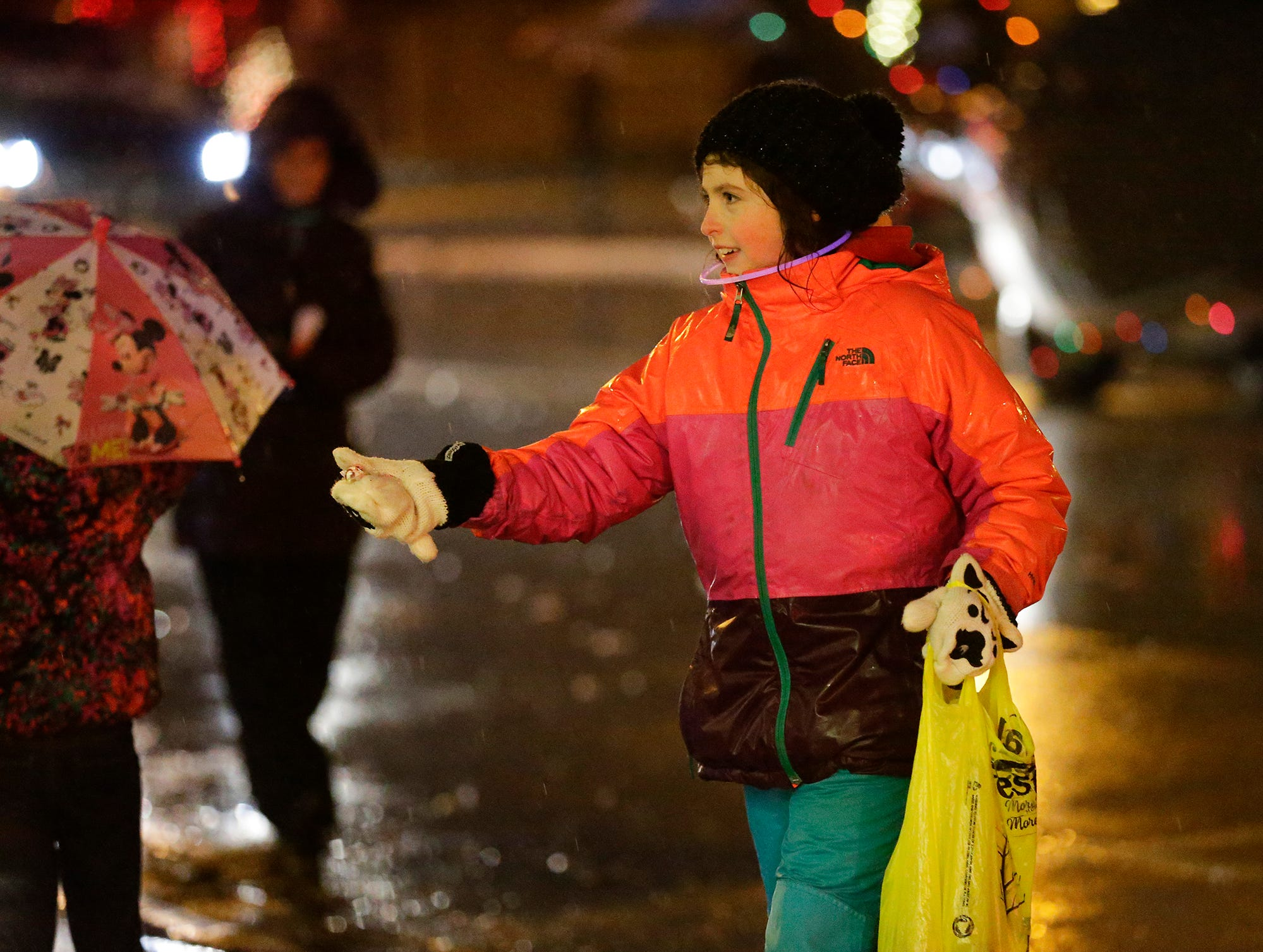 A girl hands out candy during the downtown Fond du Lac Christmas parade Saturday, December 1, 2018. Doug Raflik/USA TODAY NETWORK-Wisconsin