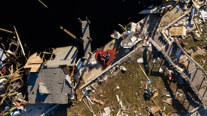 Kevin and Cyndi Lanier lay together on the heart surrounded by Hurricane Michael destruction at the canal.
