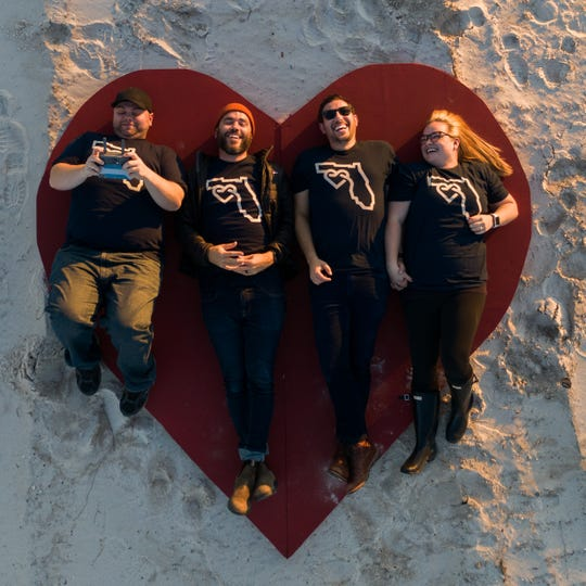 Jonathan Smith, Jeremy Cowart, Alex Workman and Chelsea Workman on the heart symbol of their Forgotten Coast Campaign.