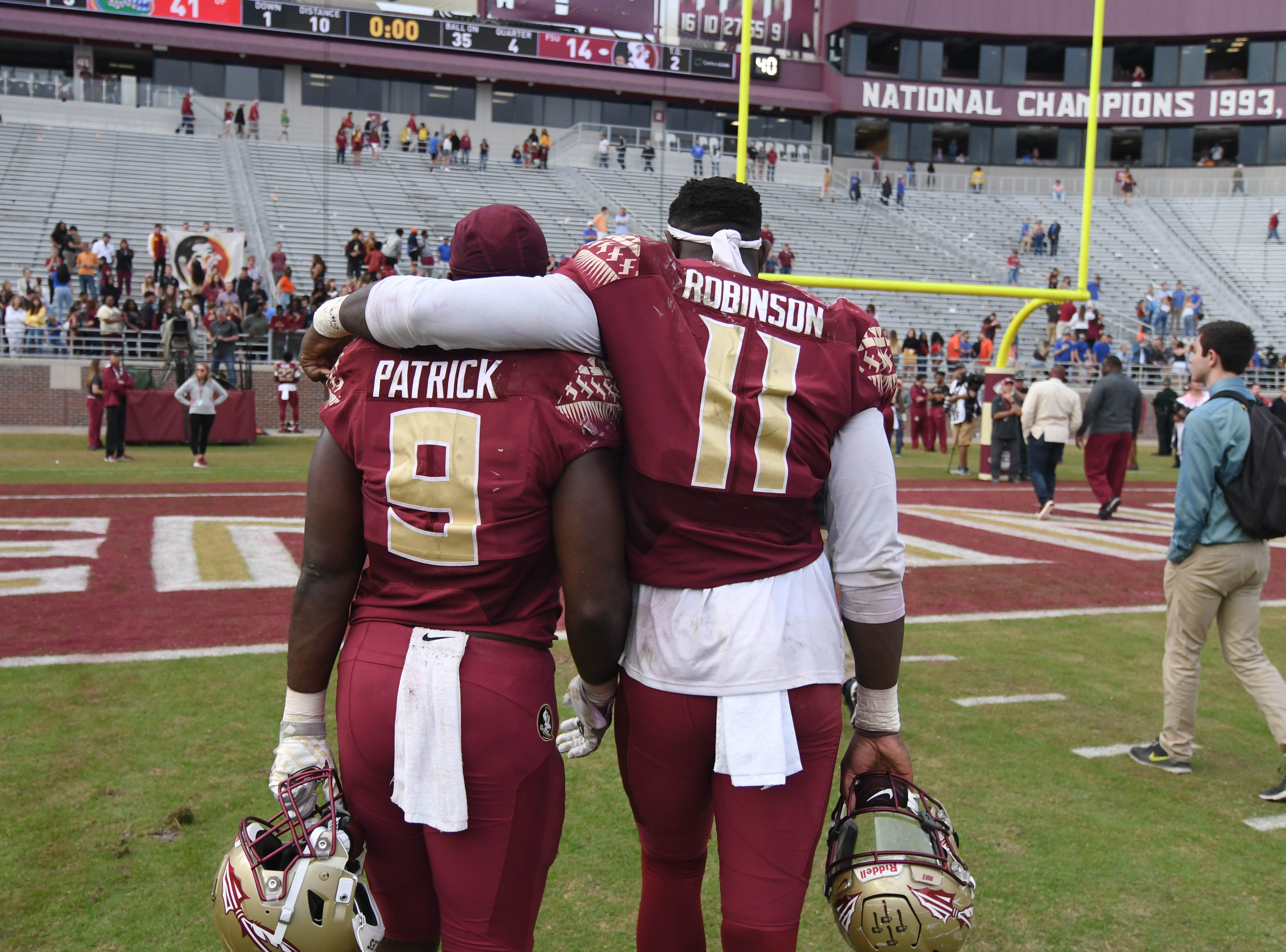 FSU senior running back Jacques Patrick (9) and FSU redshirt sophomore defensive end Janarius Robinson (11) walking off the field after the FSU game against UF at Doak Campbell Stadium on Novemeber 24, 2018.