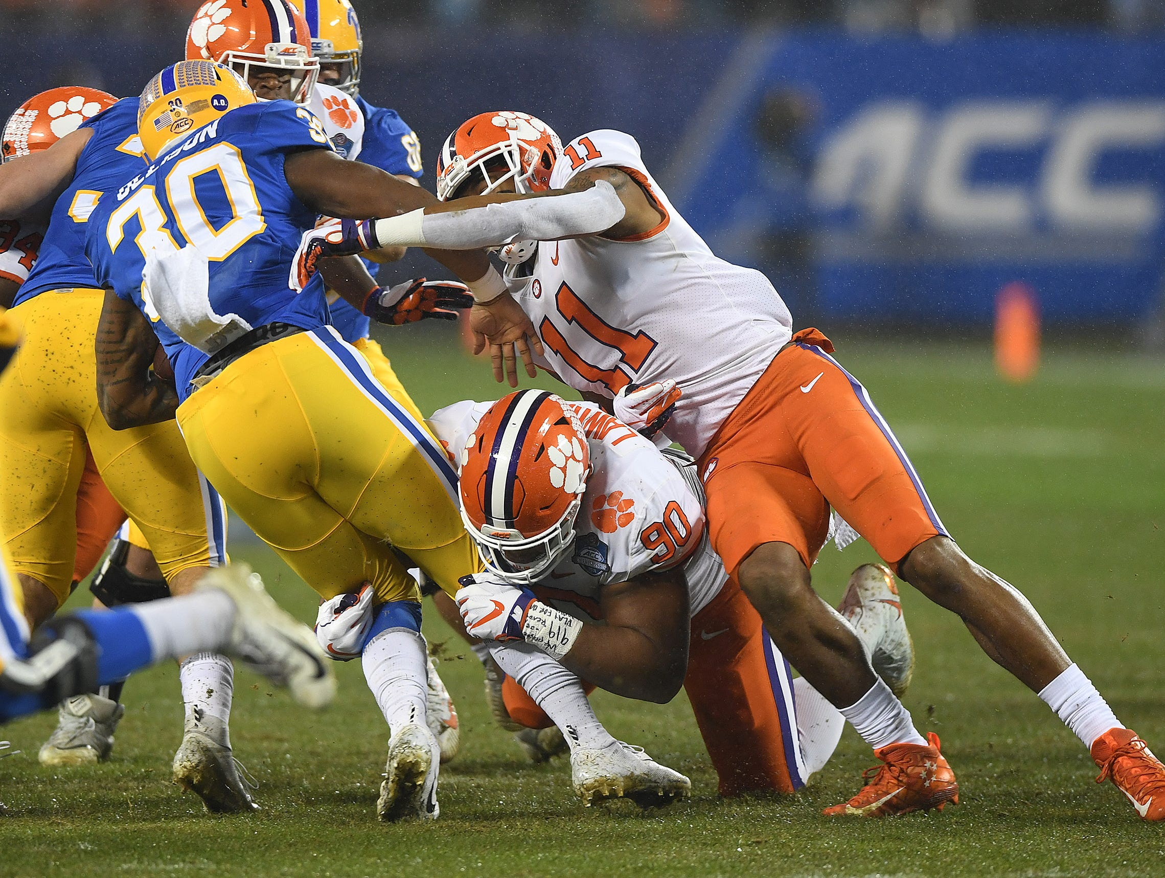 Clemson defensive lineman Dexter Lawrence (90) and safety Isaiah Simmons (11) bring down Pittsburgh running back Qadree Ollison (30) during the 1st quarter of the Dr. Pepper ACC Championship at Bank of America Stadium in Charlotte, N.C. Saturday, December 1, 2018.