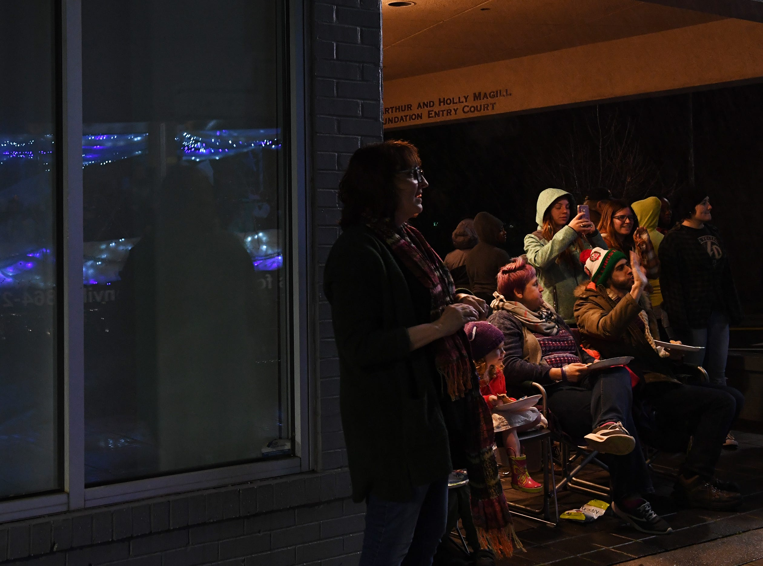 Crowds gathered inside and outside restaurants and under overhangs to keep dry during the Greenville Poinsettia Christmas Parade Saturday, Dec. 1, 2018 in downtown Greenville.