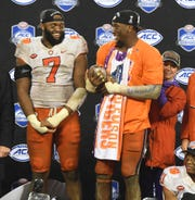 Clemson defensive linemen Austin Bryant (7), left, and Clelin Ferrell (99) with the Dr. Pepper ACC Championship trophy after the Tigers 42-10 win over Pittsburgh at Bank of America Stadium in Charlotte, N.C. Saturday, December 1, 2018.