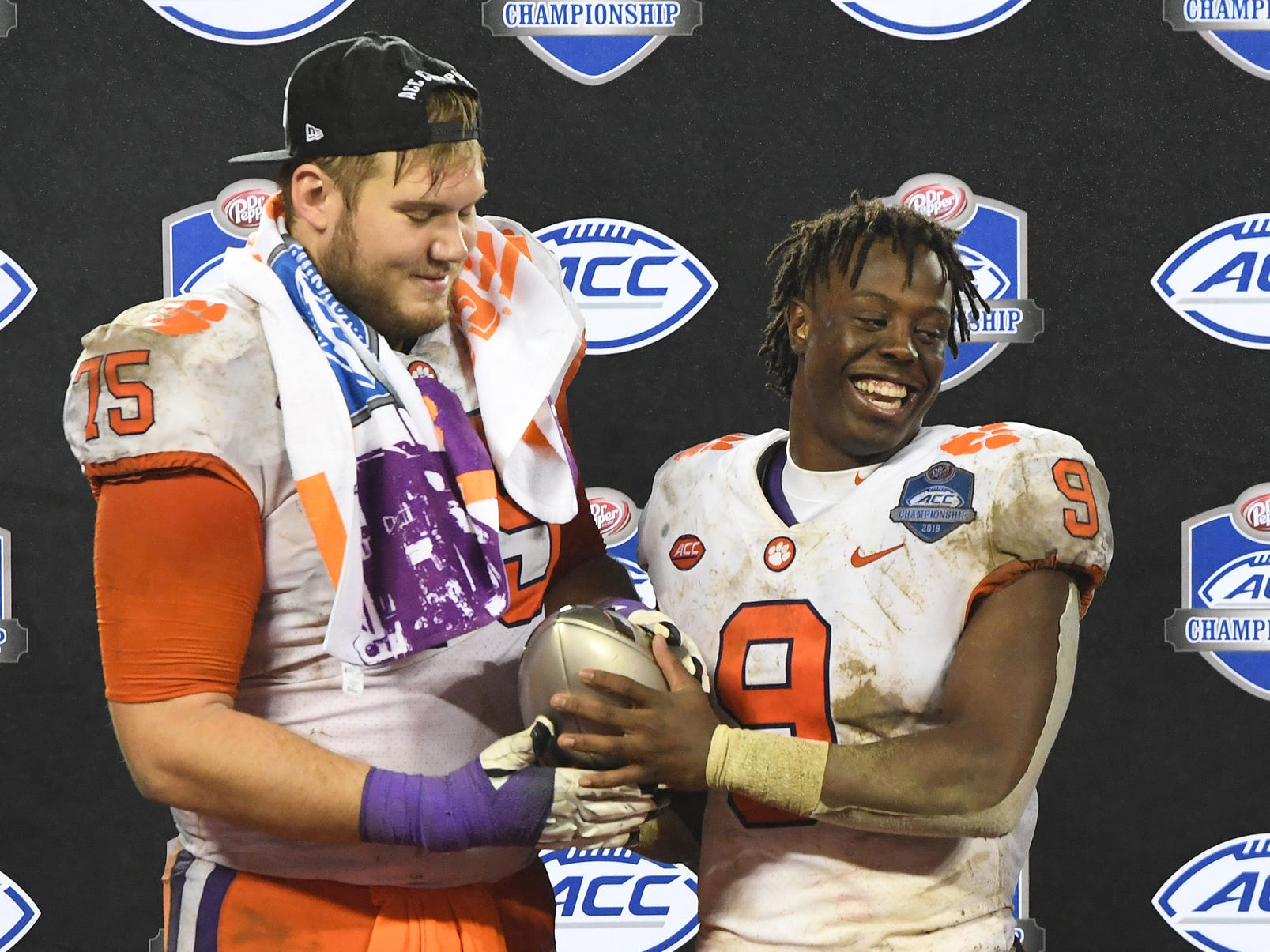 Clemson running back Travis Etienne (9) and offensive lineman Mitch Hyatt (75) hold the Dr. Pepper ACC Championship trophy after the Tigers 42-10 win over Pittsburgh at Bank of America Stadium in Charlotte, N.C. Saturday, December 1, 2018.