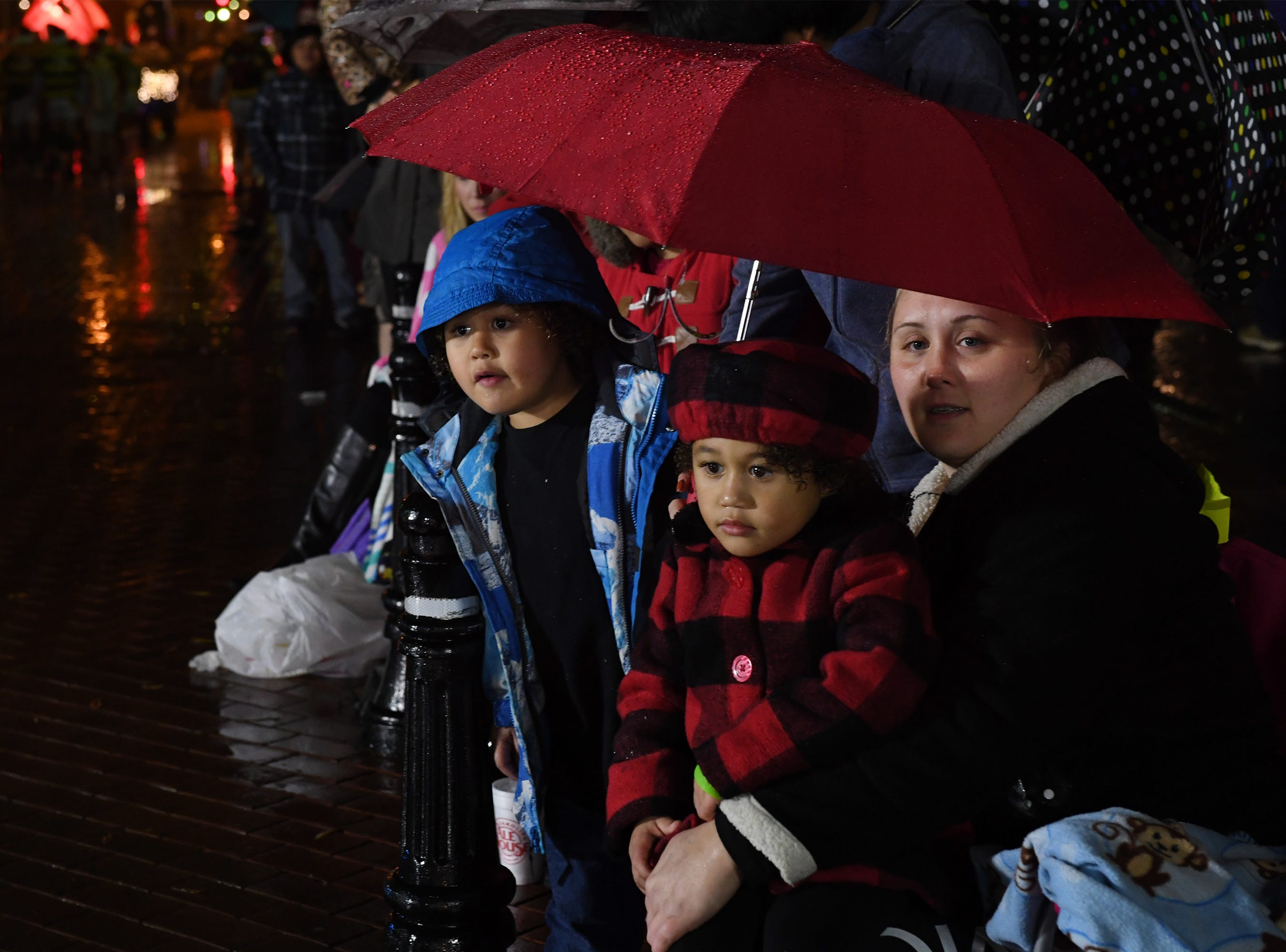Jennifer Thibeau and her kids Khloe Thibeau, 3, and Treven Lisvey, 4,watch the Greenville Poinsettia Christmas Parade Saturday, Dec. 1, 2018 in downtown Greenville.