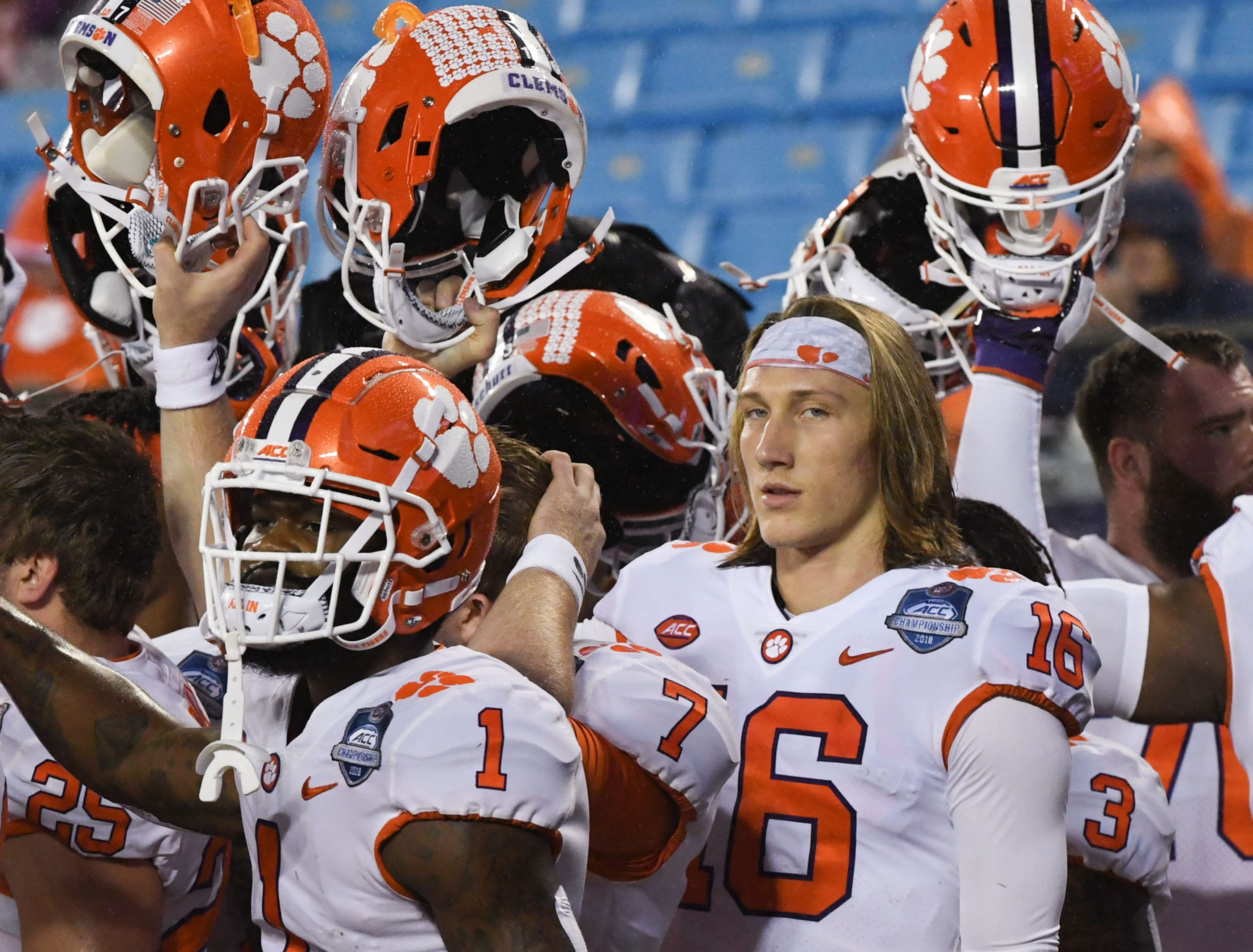 Clemson quarterback Trevor Lawrence (16) and teammates raise their helmets before the game of the Dr. Pepper ACC football championship at Bank of America Stadium in Charlotte, N.C. on Saturday, December 1, 2018.