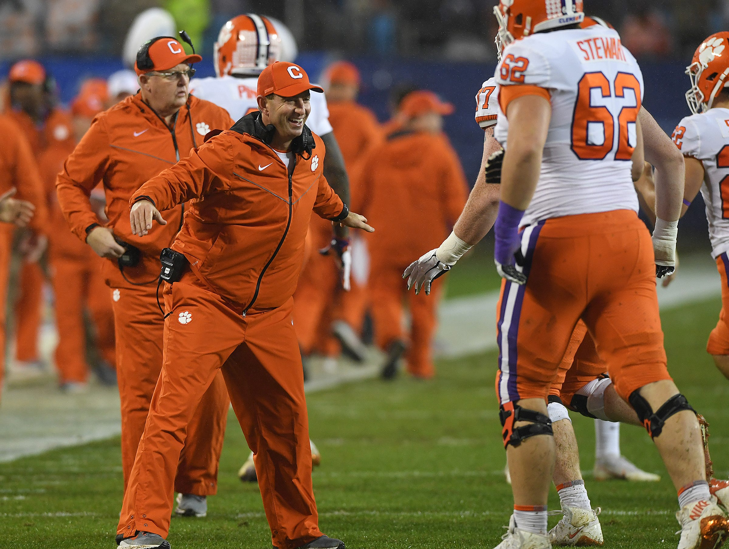 Clemson head coach Dabo Swinney congratulates the offensive line after running back Travis Etienne (9) raced 75 yards to score against Pittsburgh on the Tigers first play from scrimmage during the 1st quarter of the Dr. Pepper ACC Championship at Bank of America Stadium in Charlotte, N.C. Saturday, December 1, 2018.