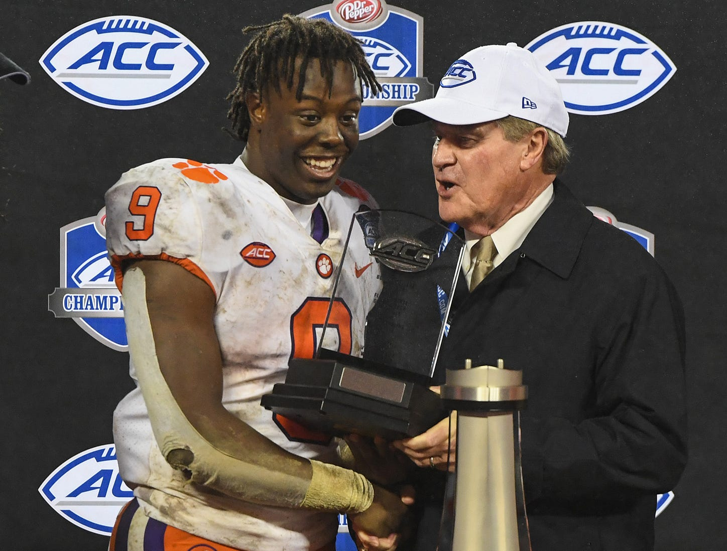 ACC Commissioner John  Swofford presents Clemson running back Travis Etienne (9) the Player of the Game trophy after the Tigers 42-10 win over Pittsburgh in the Dr. Pepper ACC Championship at Bank of America Stadium in Charlotte, N.C. Saturday, December 1, 2018.