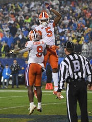 Clemson running back Travis Etienne (9) celebrates with wide receiver Tee Higgins (5) after scoring his 2nd TD of the 1st quarter against Pittsburgh of the Dr. Pepper ACC Championship at Bank of America Stadium in Charlotte, N.C. Saturday, December 1, 2018.
