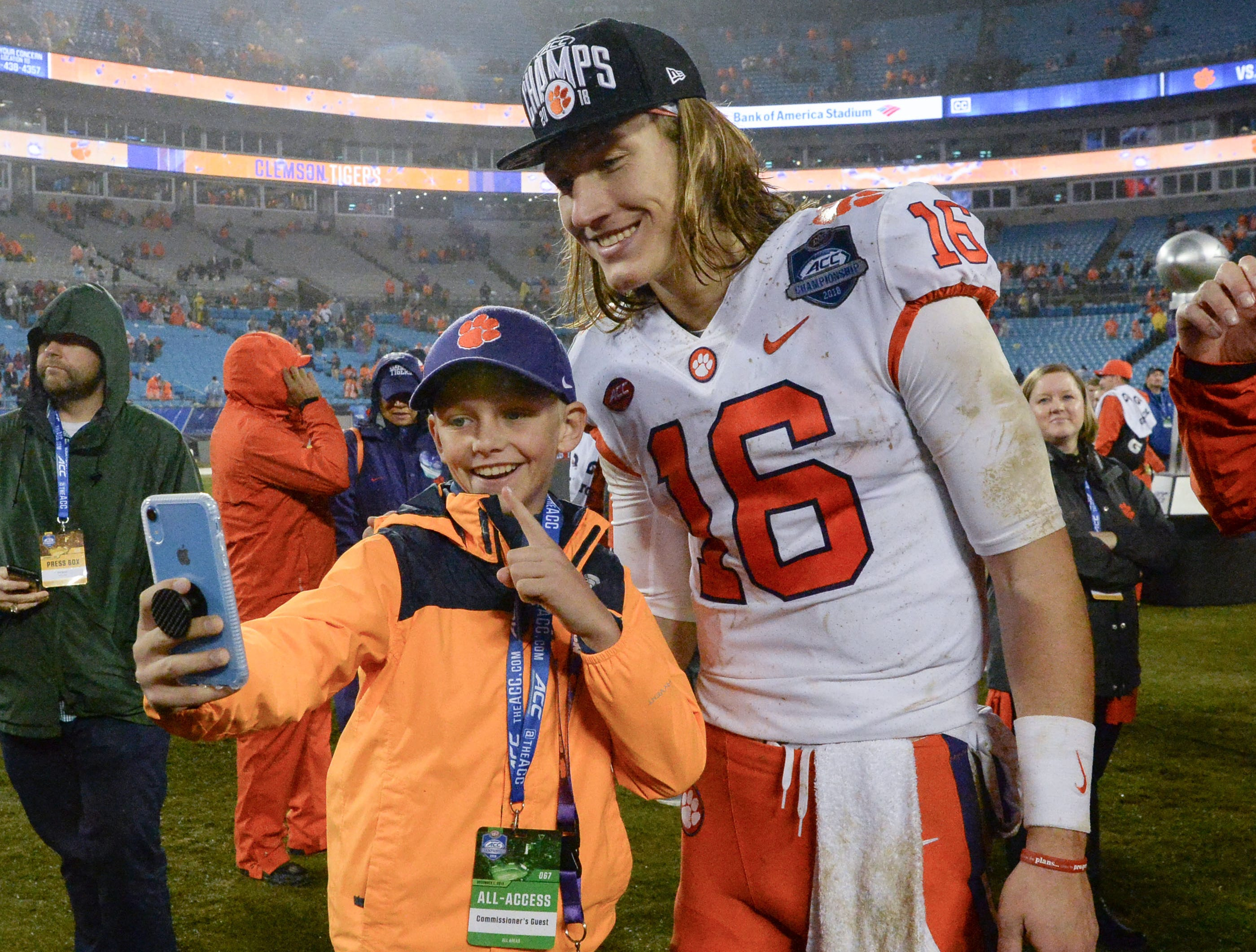 A Clemson fan poses with Clemson quarterback Trevor Lawrence (16) after the Tigers beat Pittsburgh 42-10 after the game at the Dr. Pepper ACC football championship at Bank of America Stadium in Charlotte, N.C. on Saturday, December 1, 2018.