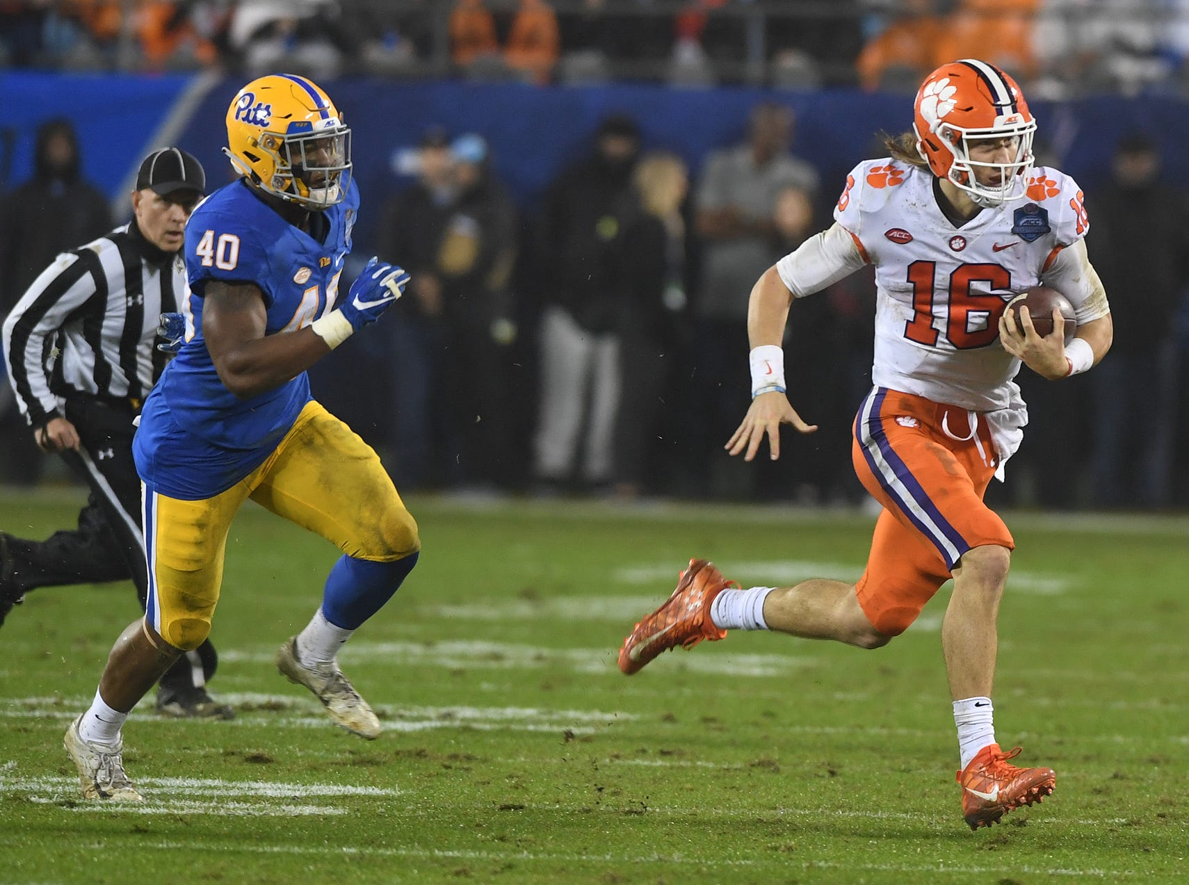 Clemson quarterback Trevor Lawrence (16) scrambles past Pittsburgh defensive end James Folston Jr. (40) during the 3rd quarter of the Dr. Pepper ACC Championship at Bank of America Stadium in Charlotte, N.C. Saturday, December 1, 2018.