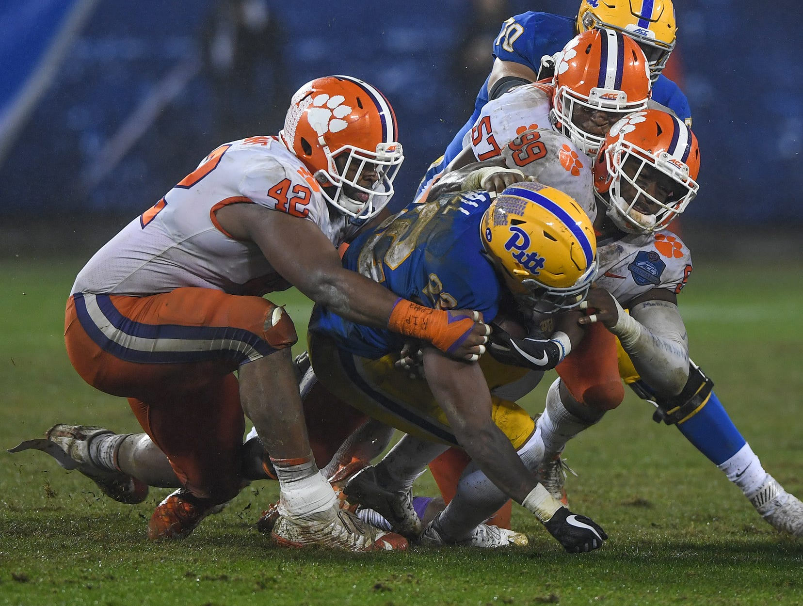 Clemson defensive lineman Christian Wilkins (42), defensive lineman Clelin Ferrell (99), and linebacker Tre Lamar (57) bring down Pittsburgh running back Darrin Hall (22) during the 3rd quarter of the Dr. Pepper ACC Championship at Bank of America Stadium in Charlotte, N.C. Saturday, December 1, 2018.