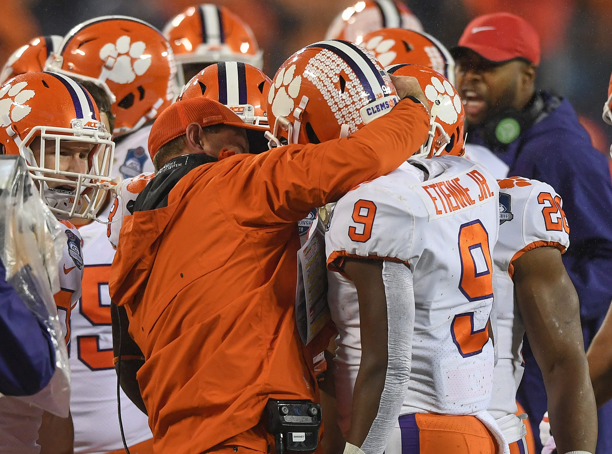 Clemson head coach Dabo Swinney congratulates running back Travis Etienne (9) after he raced 75 yards to score against Pittsburgh on the Tigers first play from scrimmage during the 1st quarter of the Dr. Pepper ACC Championship at Bank of America Stadium in Charlotte, N.C. Saturday, December 1, 2018.