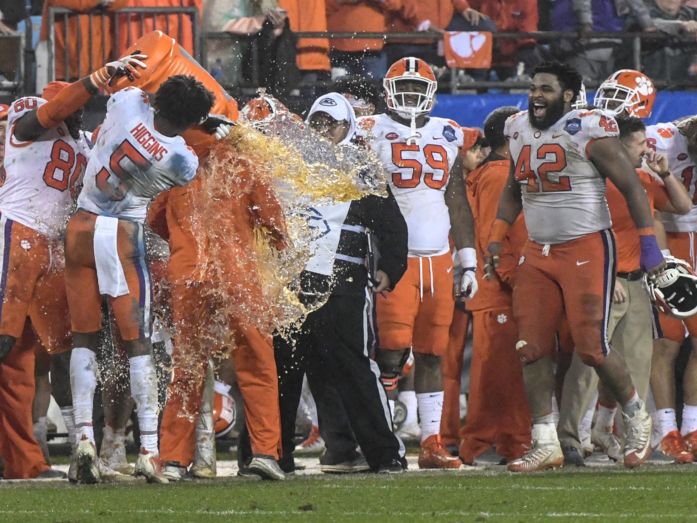 Clemson Head Coach Dabo Swinney is doused with Gatorade by Clemson tight end Milan Richard (80) and wide receiver Tee Higgins (5) during the fourth quarter in Memorial Stadium on Saturday, November 3, 2018.