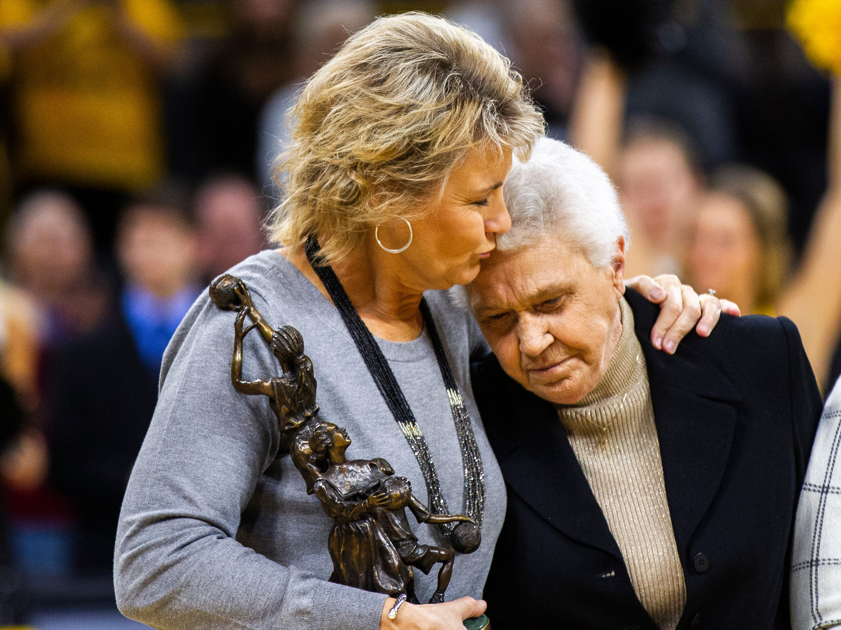 Iowa head coach Lisa Bluder, left, shares a moment with Christine Grant while she is acknowledged for being induced into the women's basketball hall of fame before a NCAA women's basketball game on Sunday, Dec. 2, 2018, at Carver-Hawkeye Arena in Iowa City.