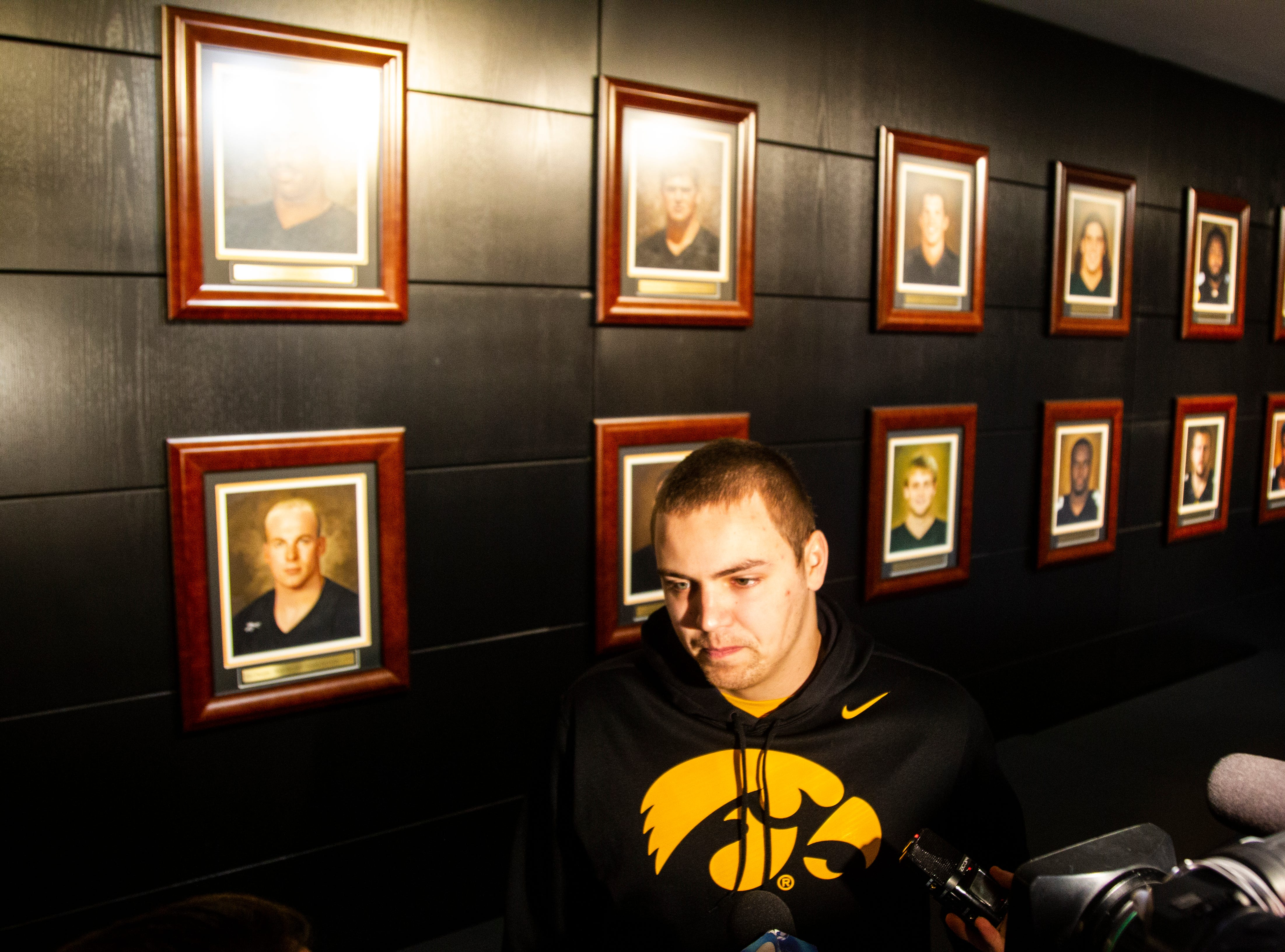 Iowa quarterback Nate Stanley (4) talks with reporters in front of portraits of Iowa Consensus All Americans during an Outback Bowl announcement press conference on Sunday, Dec. 2, 2018, at the Hansen Football Performance Center in Iowa City.