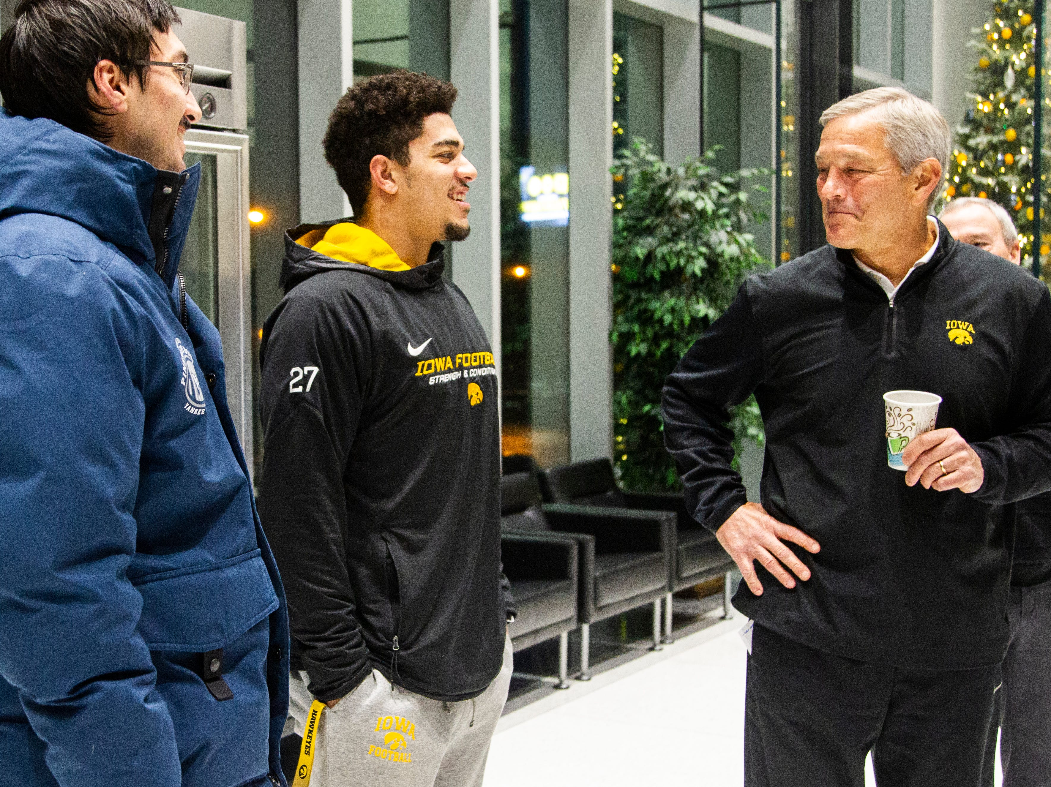 Iowa football head coach Kirk Ferentz talks with Iowa defensive back Amani Hooker (center) and Iowa placekicker Miguel Recinos (left) during an Outback Bowl announcement press conference on Sunday, Dec. 2, 2018, at the Hansen Football Performance Center in Iowa City.