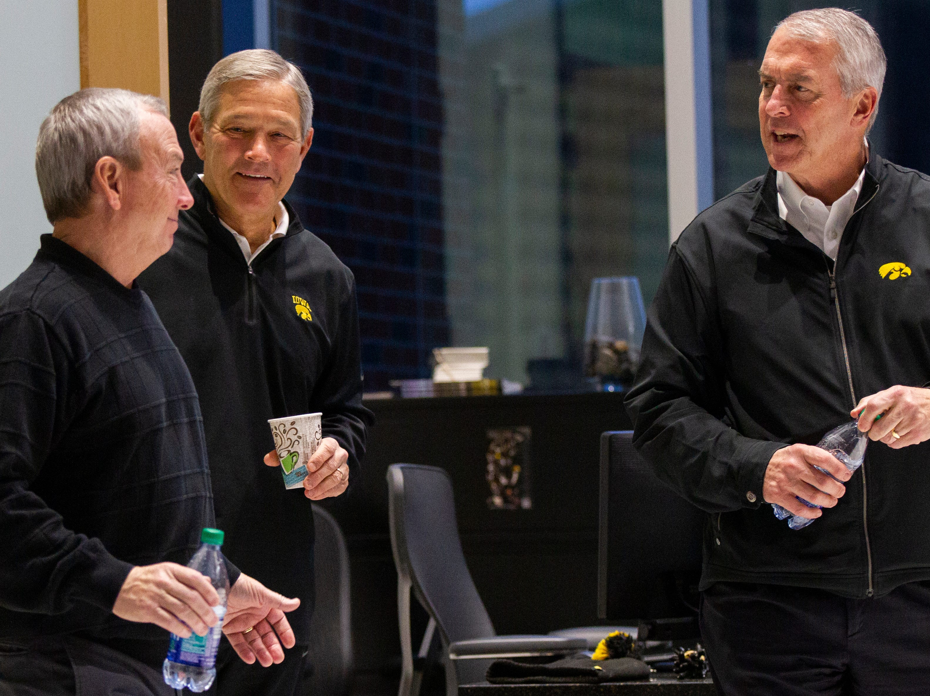 Iowa football head coach Kirk Ferentz and athletic director Gary Barta talk with assistant athletic director Steve Roe (far left) before an Outback Bowl announcement press conference on Sunday, Dec. 2, 2018, at the Hansen Football Performance Center in Iowa City.