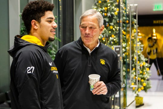 Iowa head coach Kirk Ferentz talks with Amani Hooker, who was named the Big Ten's defensive back of the year, after his bowl-announcement press conference.