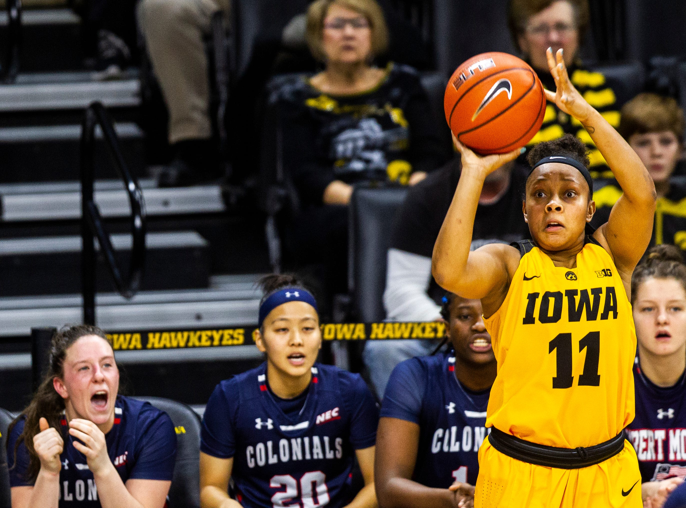 Iowa guard Tania Davis (11) shoots a 3-point basket in front of the Robert Morris bench during a NCAA women's basketball game on Sunday, Dec. 2, 2018, at Carver-Hawkeye Arena in Iowa City.
