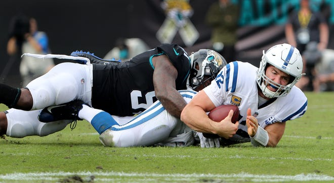 Indianapolis Colts quarterback Andrew Luck (12) is sacked by Jacksonville Jaguars defensive end Yannick Ngakoue (91) in the second quarter of their game at TIAA Bank Field on Thursday, Dec. 2, 2018.