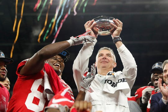 Ohio State Buckeyes coach Urban Meyer and wide receiver Terry McLaurin (83) hold up the trophy after defeating the Northwestern Wildcats in the Big Ten conference championship game at Lucas Oil Stadium.