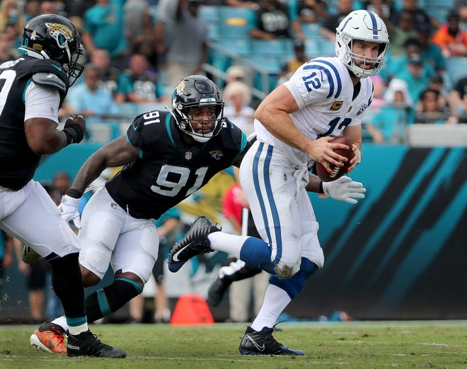 Indianapolis Colts quarterback Andrew Luck (12) is chased out of the pocket by Jacksonville Jaguars defensive end Yannick Ngakoue (91) in the second quarter of their game at TIAA Bank Field on Thursday, Dec. 2, 2018.