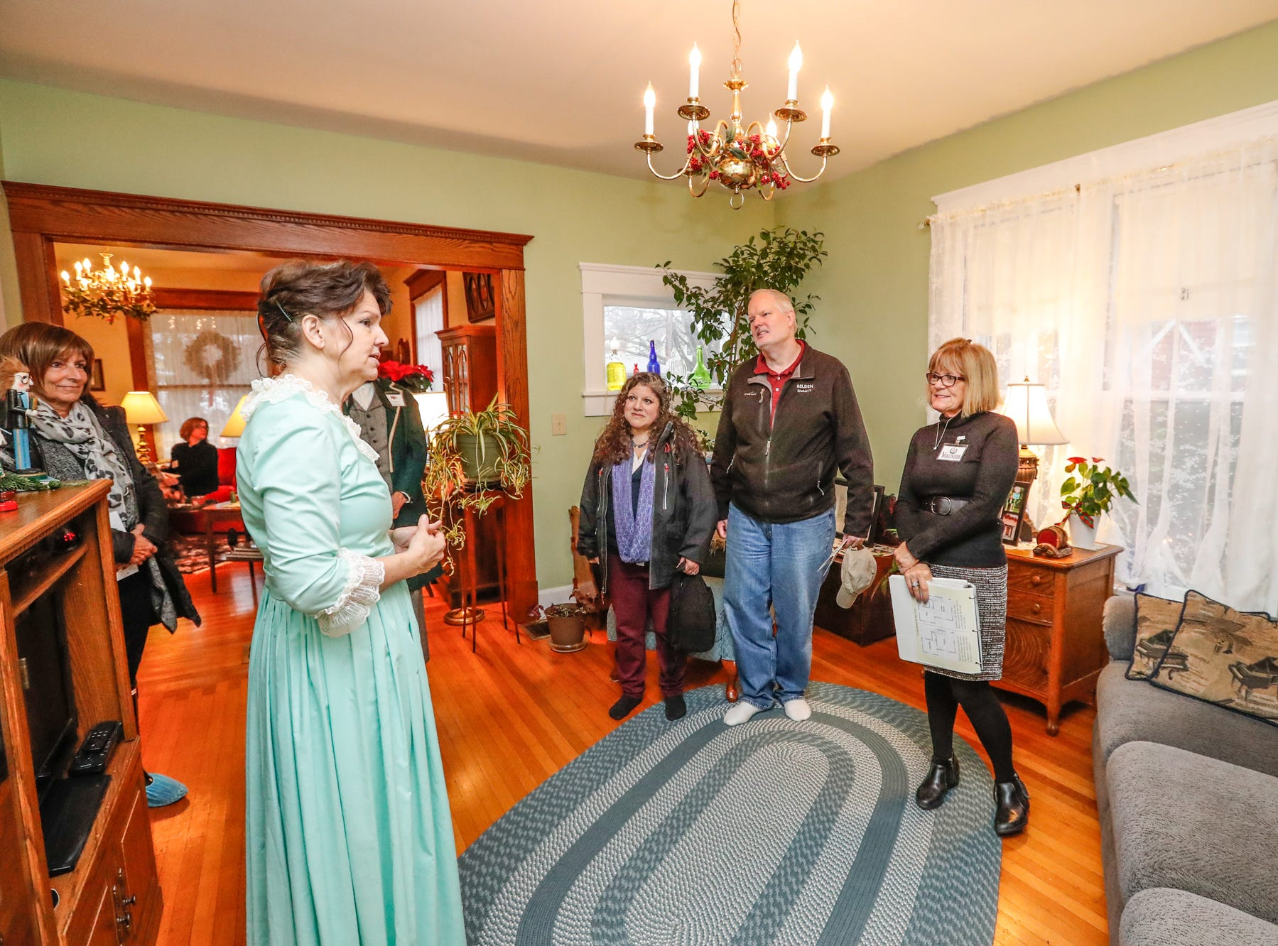 Ruth Schwartz, center left, wears the dress she sewed for her period wedding while speaking to guests during the Carmel Clay Historical Society Holiday Home Tour of her 1903 home in Carmel Ind. on Saturday, Dec.1, 2018.