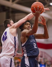 La Lumiere High School senior Keion Brooks, Jr. (12) is fouled by Brownsburg High School senior Ryan Wiggins (42) as he puts up a shot at Danville High School.