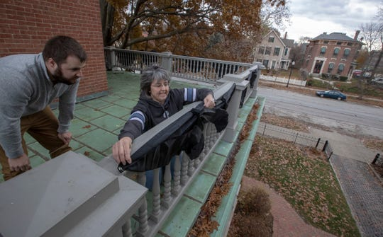 Mourning bunting being installed by Lukas Ramey (left), a volunteer manager, and Jennifer Capps, VP for Curatorship and Exhibition, at the Benjamin Harrison Presidential Site, Indianapolis, Sunday, Dec. 2, 2018. This display on the railings, and a half-mast flag, pay respects to George H. W. Bush, the 41st President, who died on Friday evening in Houston.