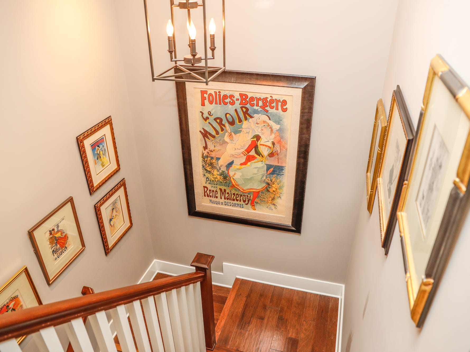 Colorful vintage prints decorate the stairwell at the home of Brad Sexauer during the Carmel Clay Historical Society Holiday Home Tour in Carmel Ind. on Saturday, Dec.1, 2018. The home features an array of fine art, and an open concept floor plan.