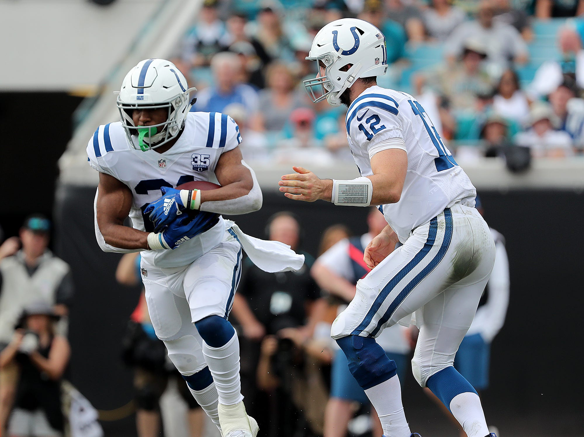 Indianapolis Colts quarterback Andrew Luck (12) hands the ball off to running back Nyheim Hines (21) in the second quarter of their game at TIAA Bank Field on Thursday, Dec. 2, 2018.