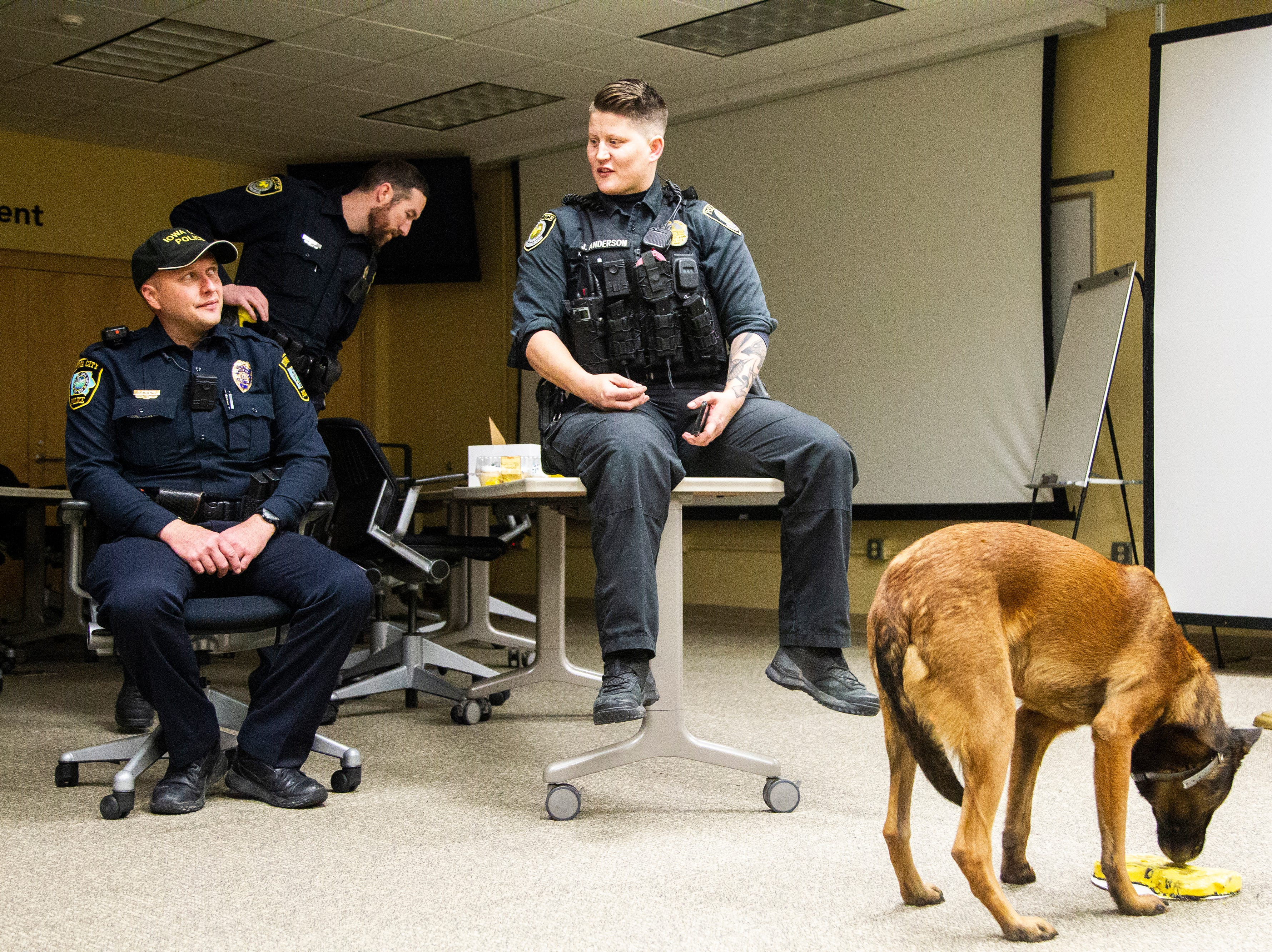 Officer Jackie Anderson, center, talks with Doug Roling, a bomb technician for the Iowa City Police Department, while K9 Falo licks his retirement cake on Saturday, Dec. 1, 2018, at the University of Iowa Police Department at the Old Capitol Town Center in Iowa City.